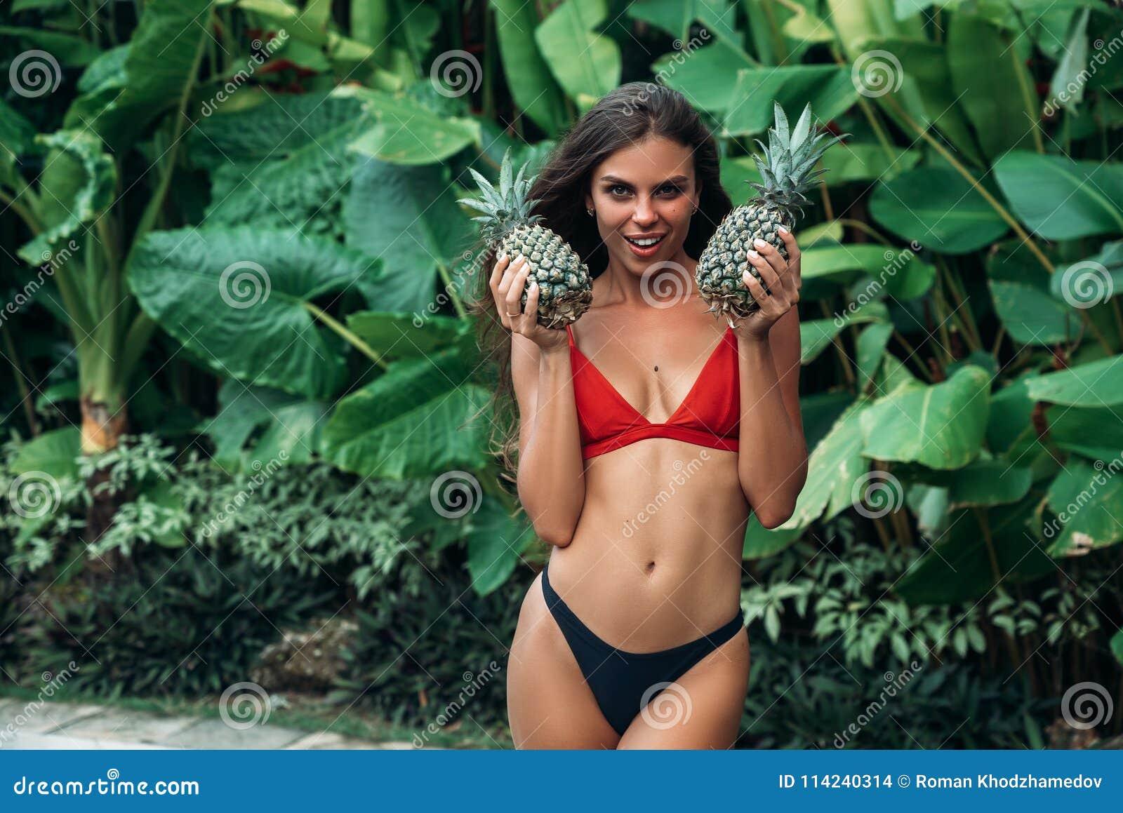 La fille de brune rit Beau modèle dans un maillot de bain avec l ananas dans des mains souriant et posant contre a