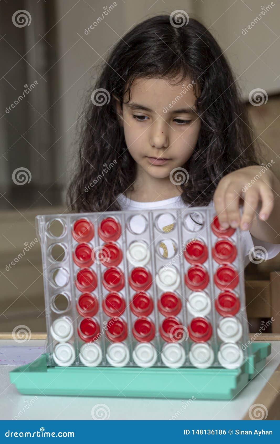 La fille de cheveux noirs jouant avec le boardgame