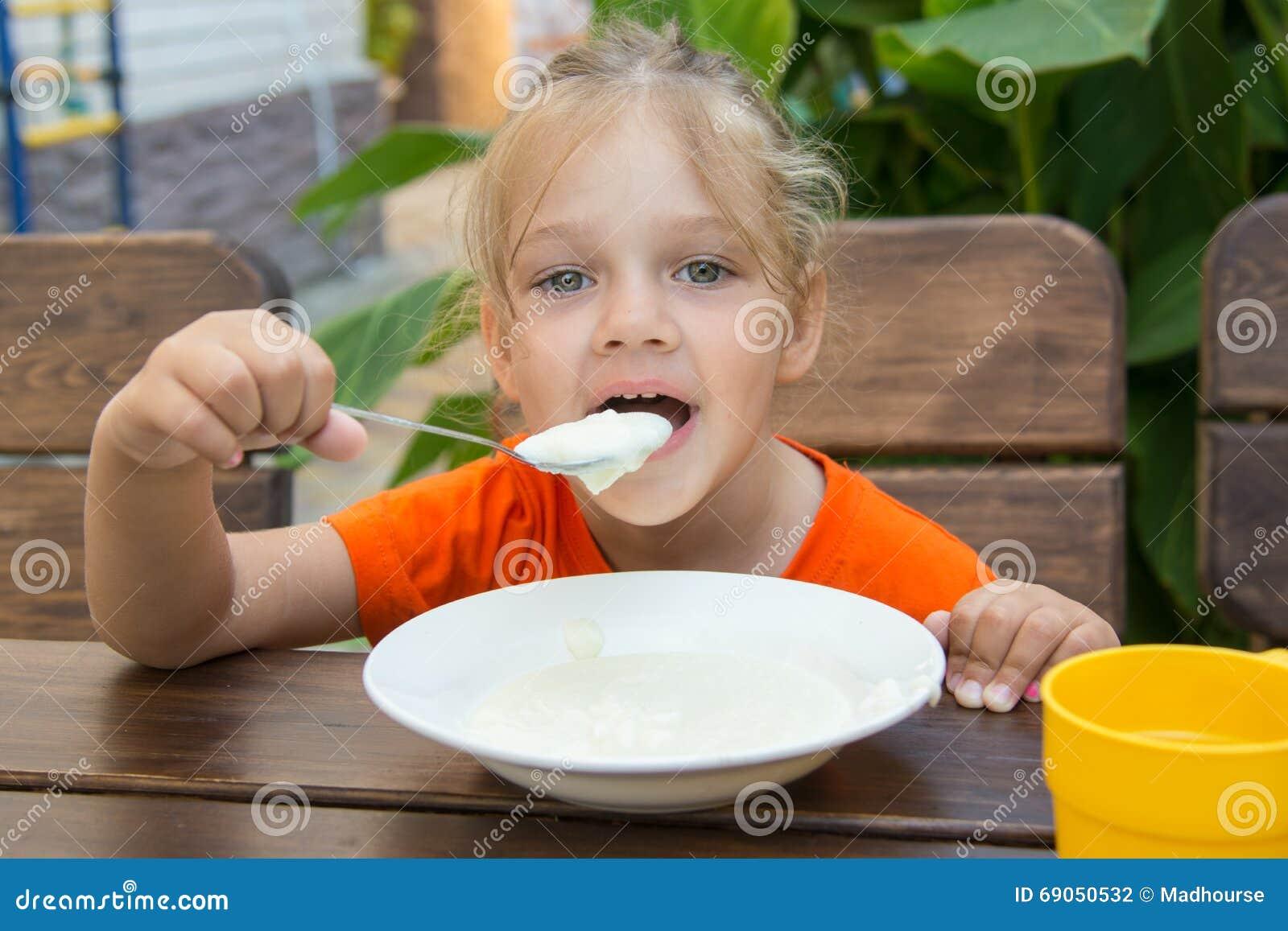 La fille de cinq ans drôle avec plaisir mange du gruau pour le petit déjeuner