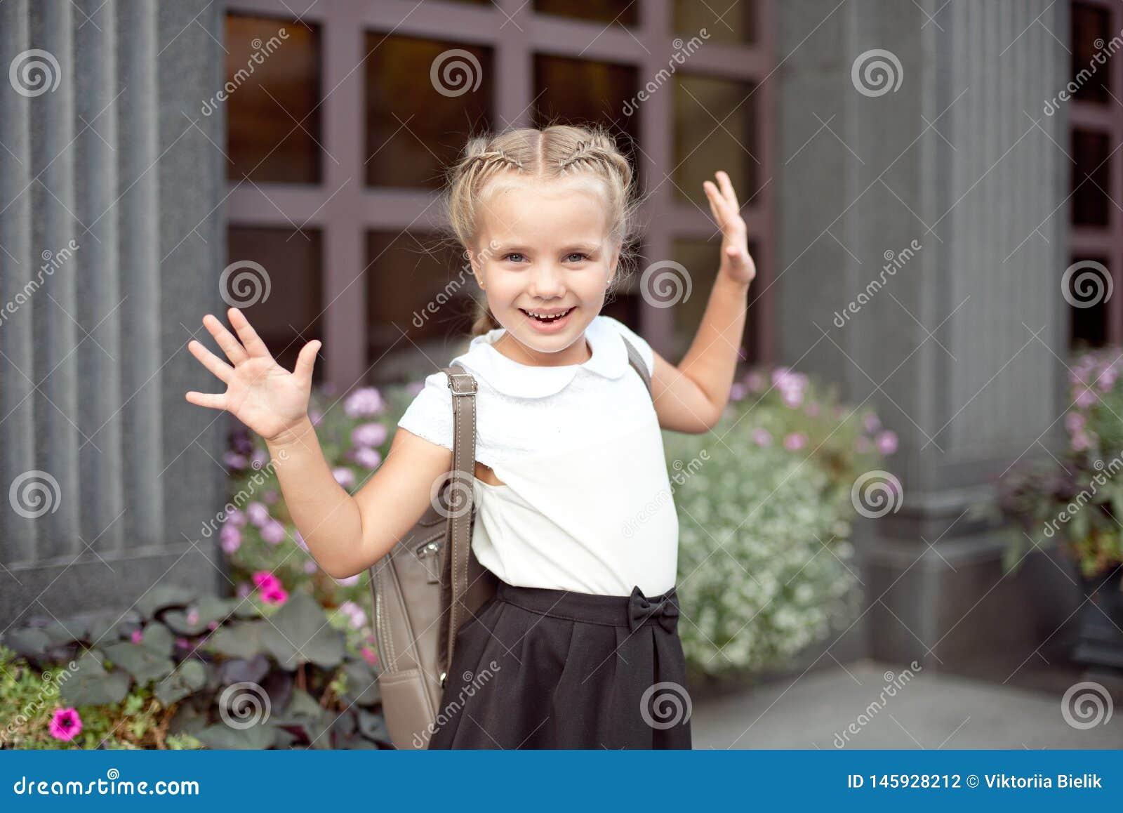 La fille de sourire heureuse va instruire pour la premi?re fois avec le sac vont ? l ?cole primaire