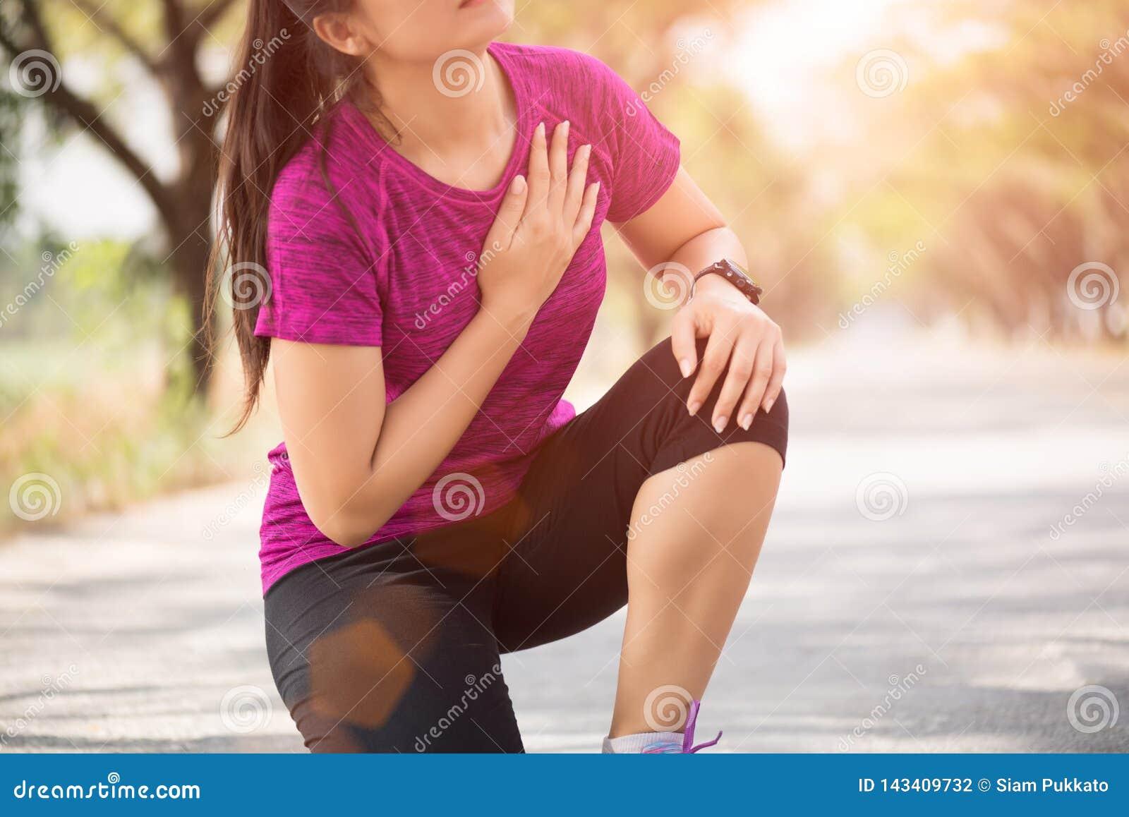 La fille de sport ont la douleur thoracique après avoir pulsé ou en courant établissez en parc Concept de sport et de soins de sa