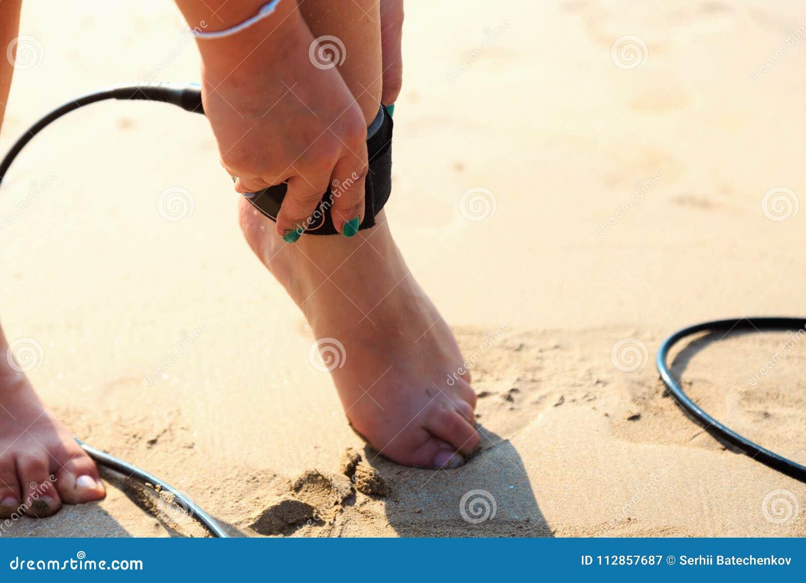 La fille de surfer attache la laisse à la jambe
