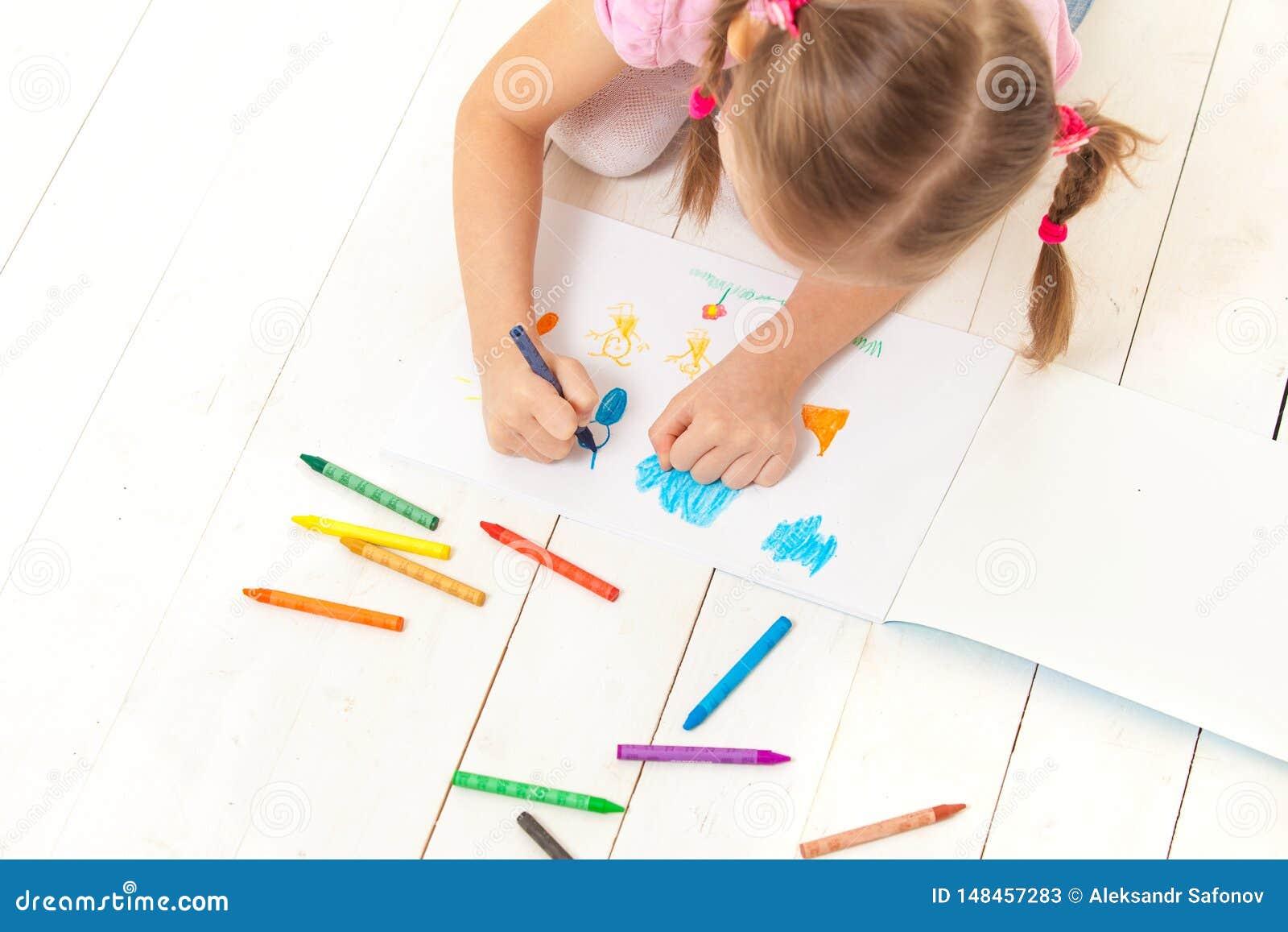 La fille dessine avec des crayons dans l album