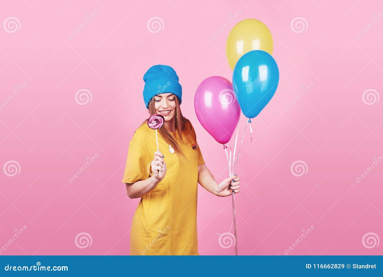 La fille drôle mignonne en portrait de chapeau bleu tient les ballons colorés et la lucette d un air souriant sur le fond rose Be