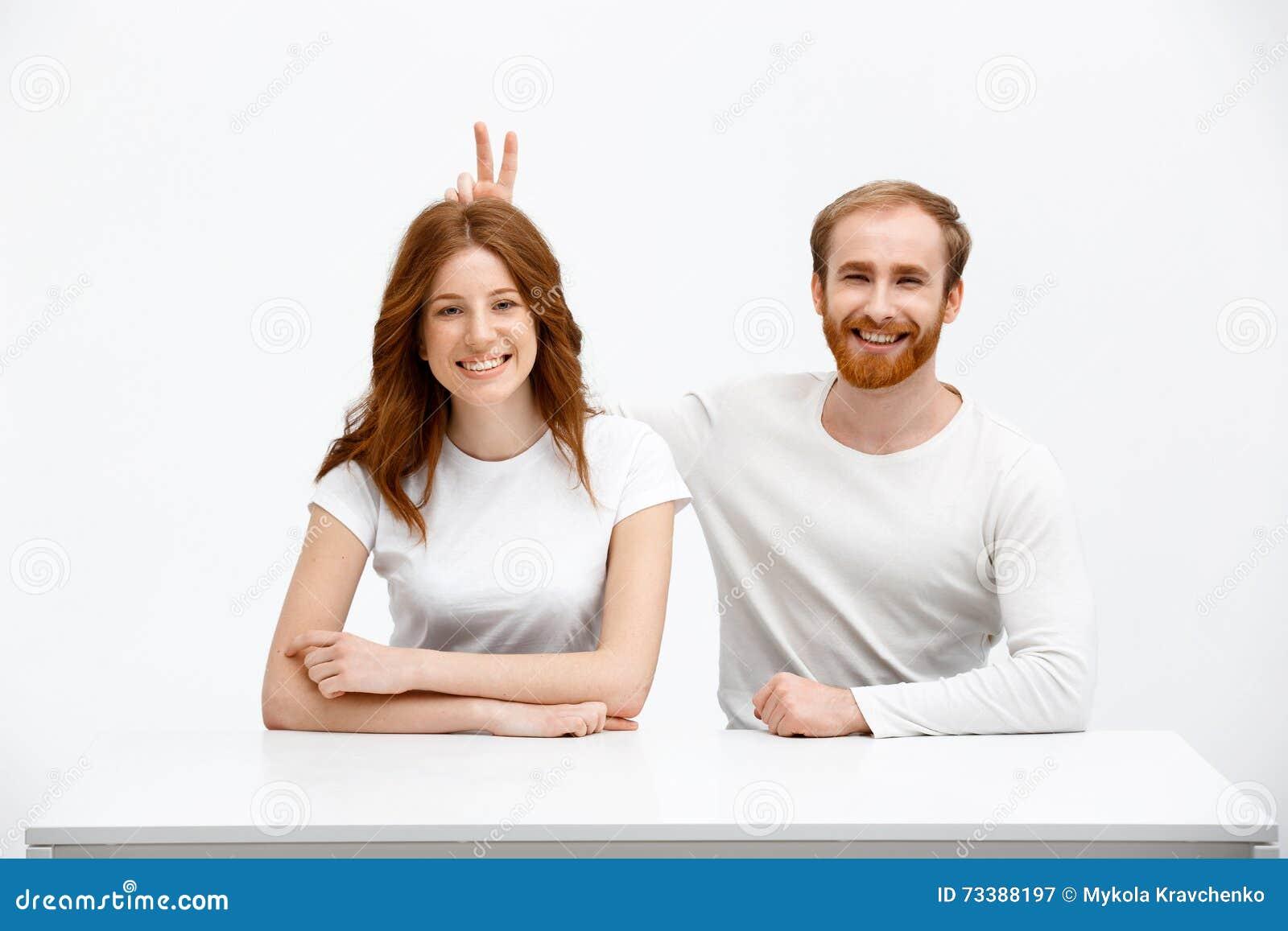 La fille drôle et le garçon roux s asseyant au bureau blanc jouent