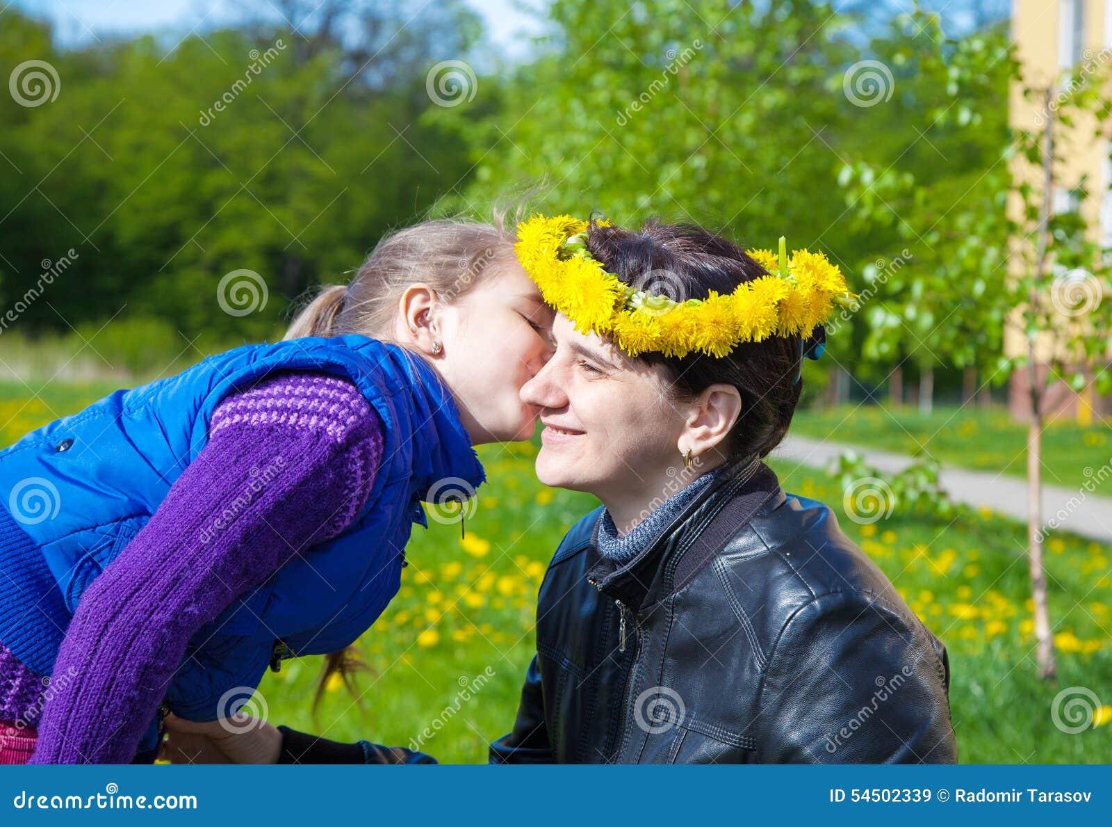 La fille embrasse la maman en parc