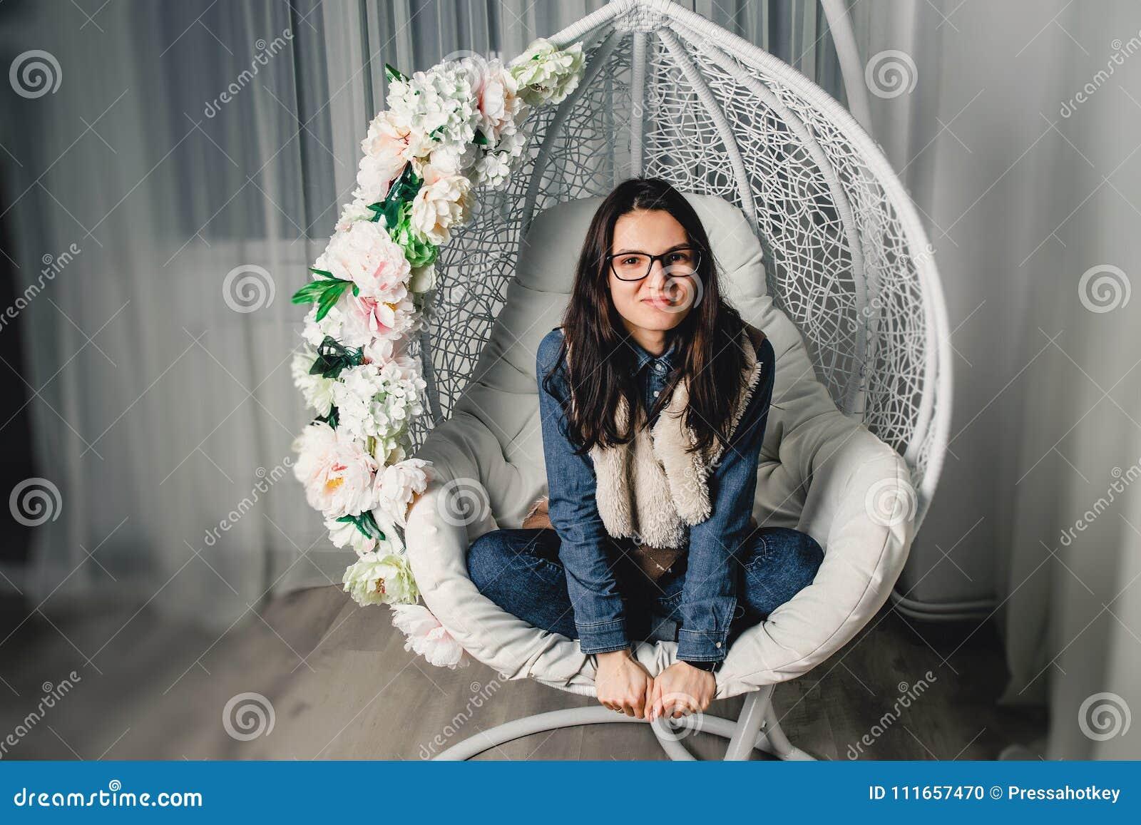 La fille en verres s assied sur une oscillation ronde et sourit