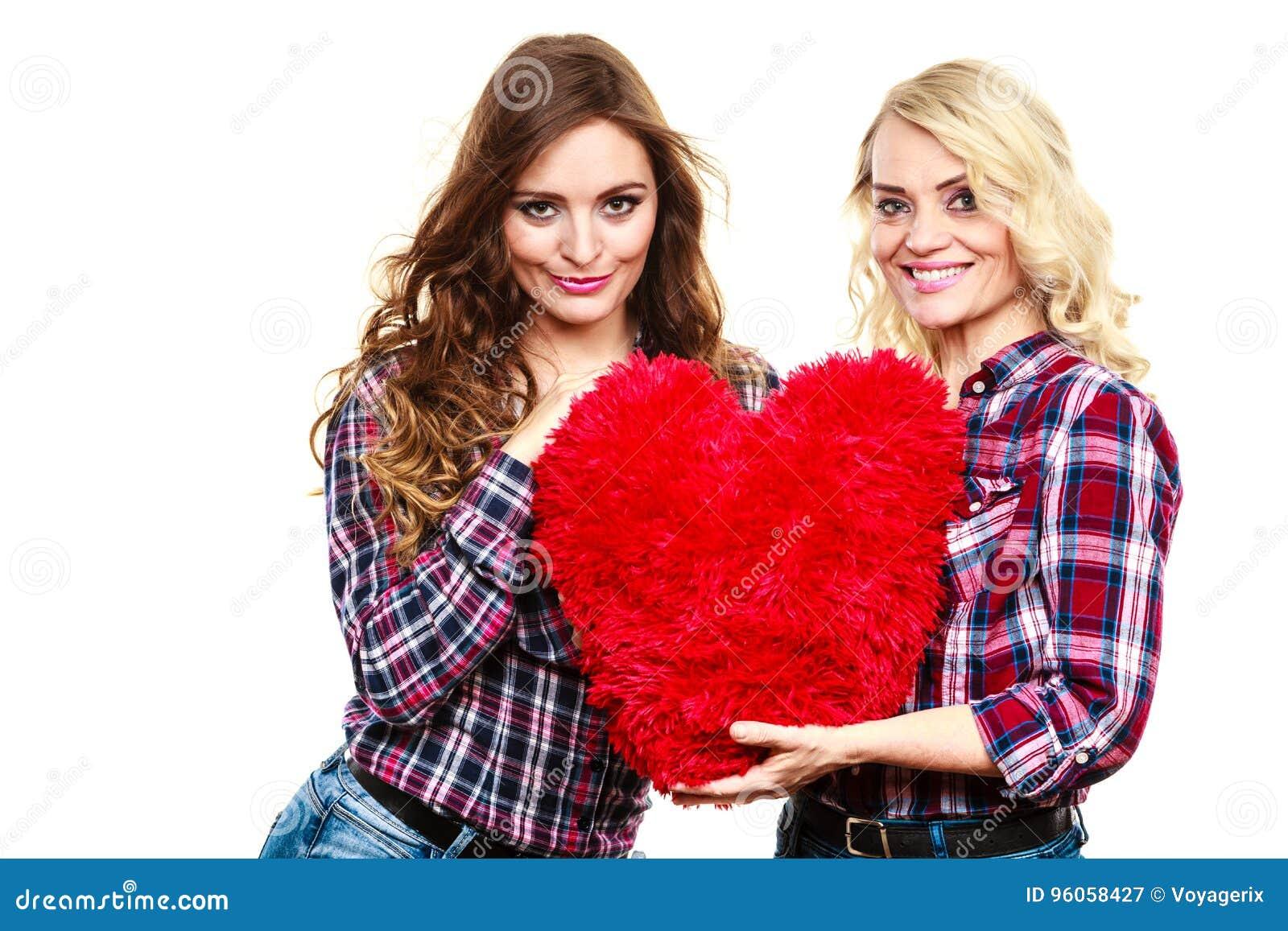 La fille et la mère adultes avec le coeur aiment le signe
