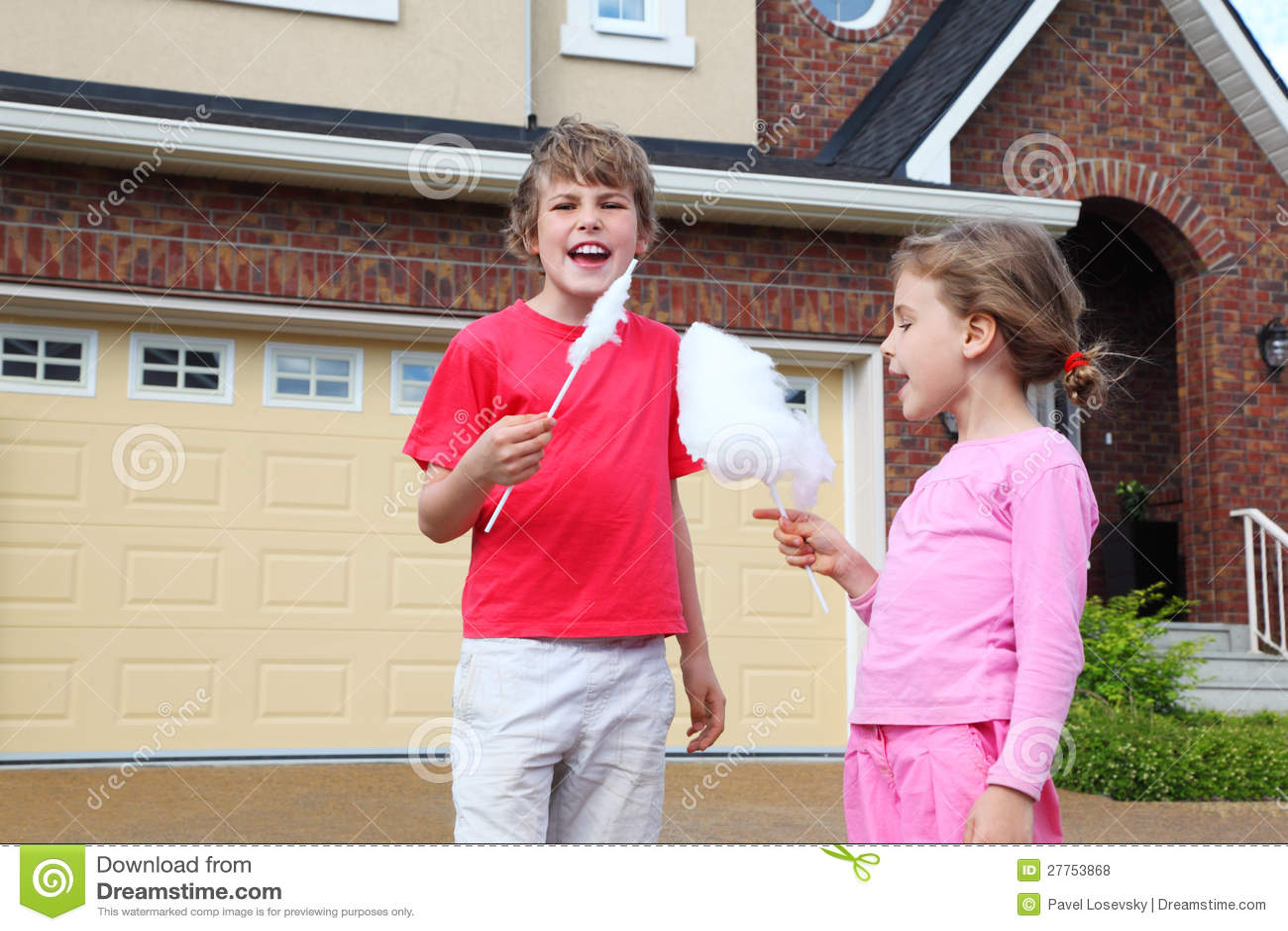 La fille et le garçon heureux avec la sucrerie de coton crient