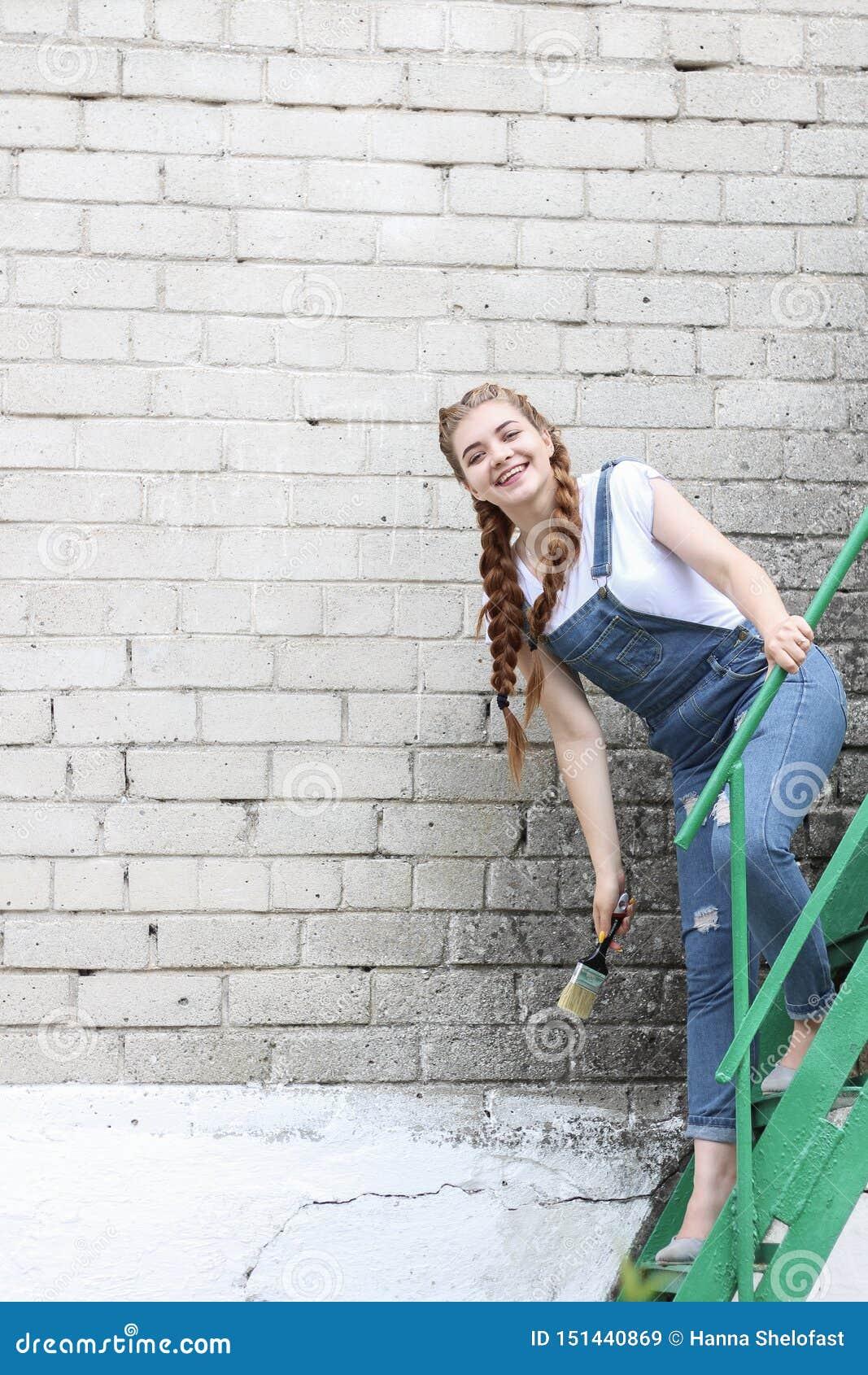 La fille fait la préparation à peindre un belvédère extérieur en bois, barrière