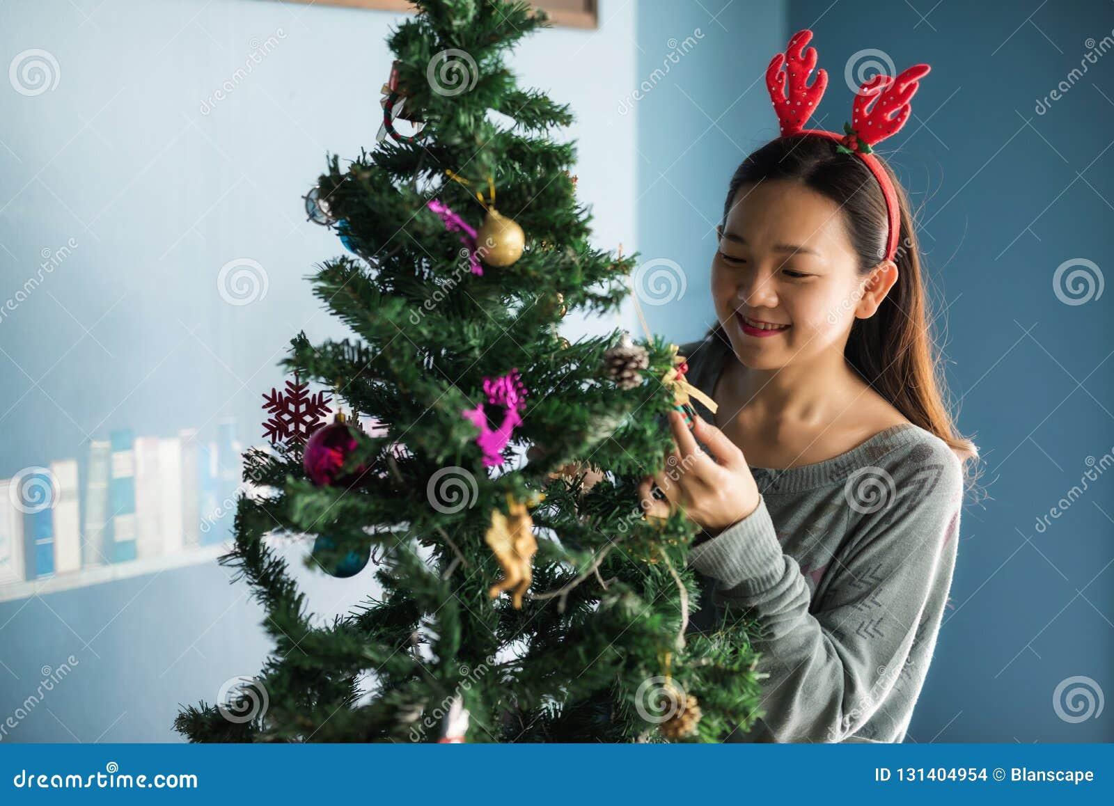 La fille heureuse chinoise asiatique avec le costume de renne décorent des cadeaux sur l arbre de Noël La femme mignonne attirant