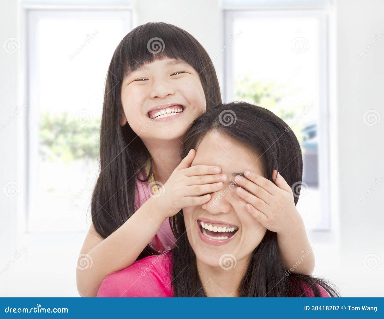La fille heureuse couvrent ses yeux de mère