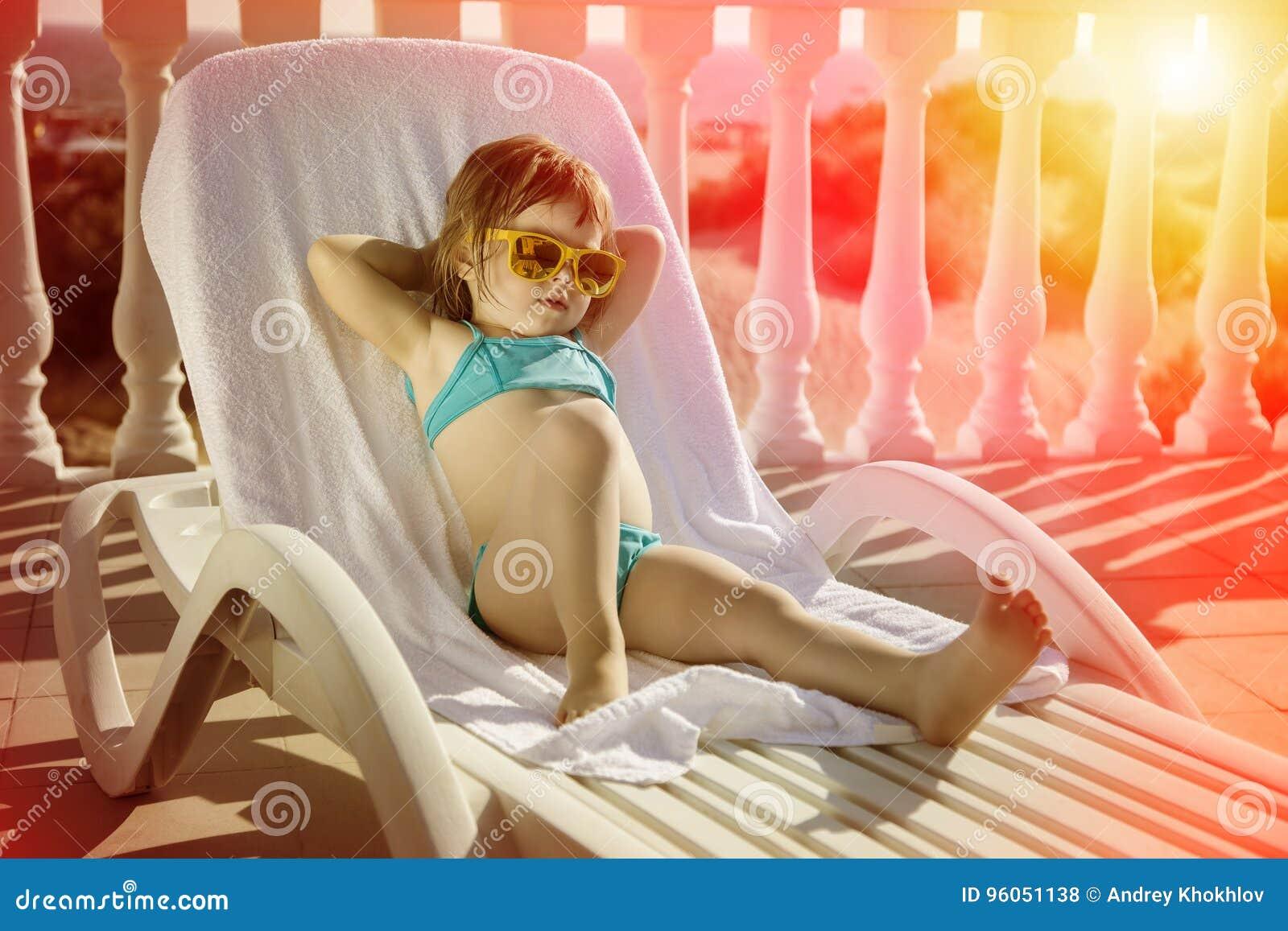 La fille heureuse détend dans un canapé du soleil au coucher du soleil