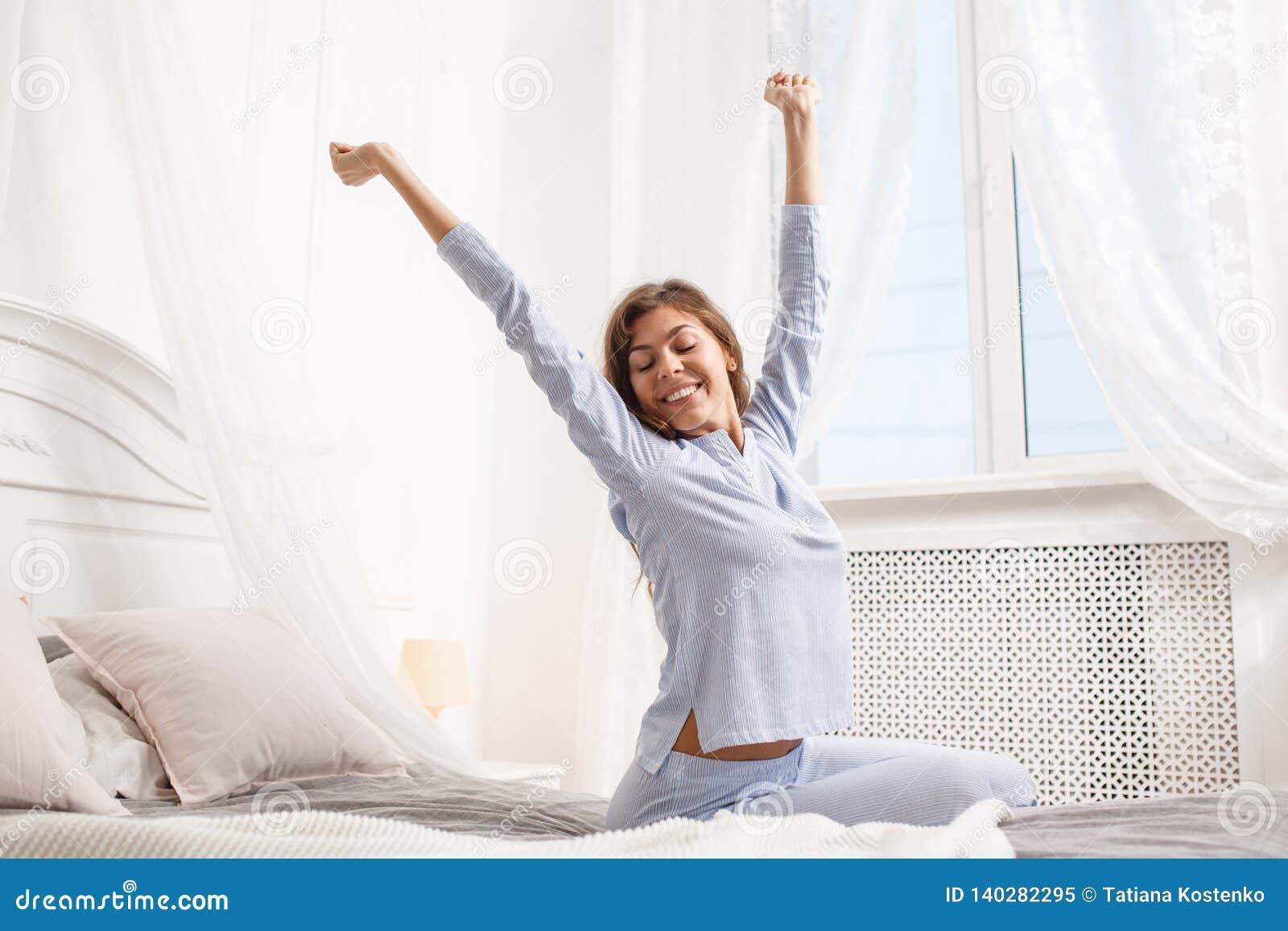 La fille heureuse de brune dans le pyjama bleu-clair étire ses bras vers le haut de se reposer sur le lit d auvent à côté de la f