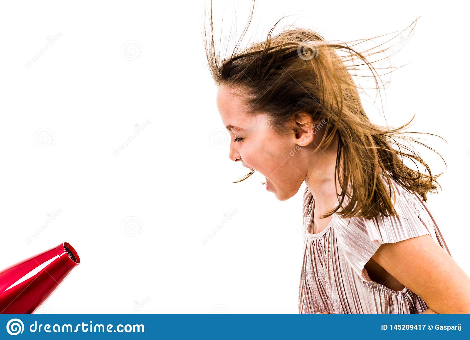La fille hurle, criant au dessiccateur de coup - s?che-cheveux