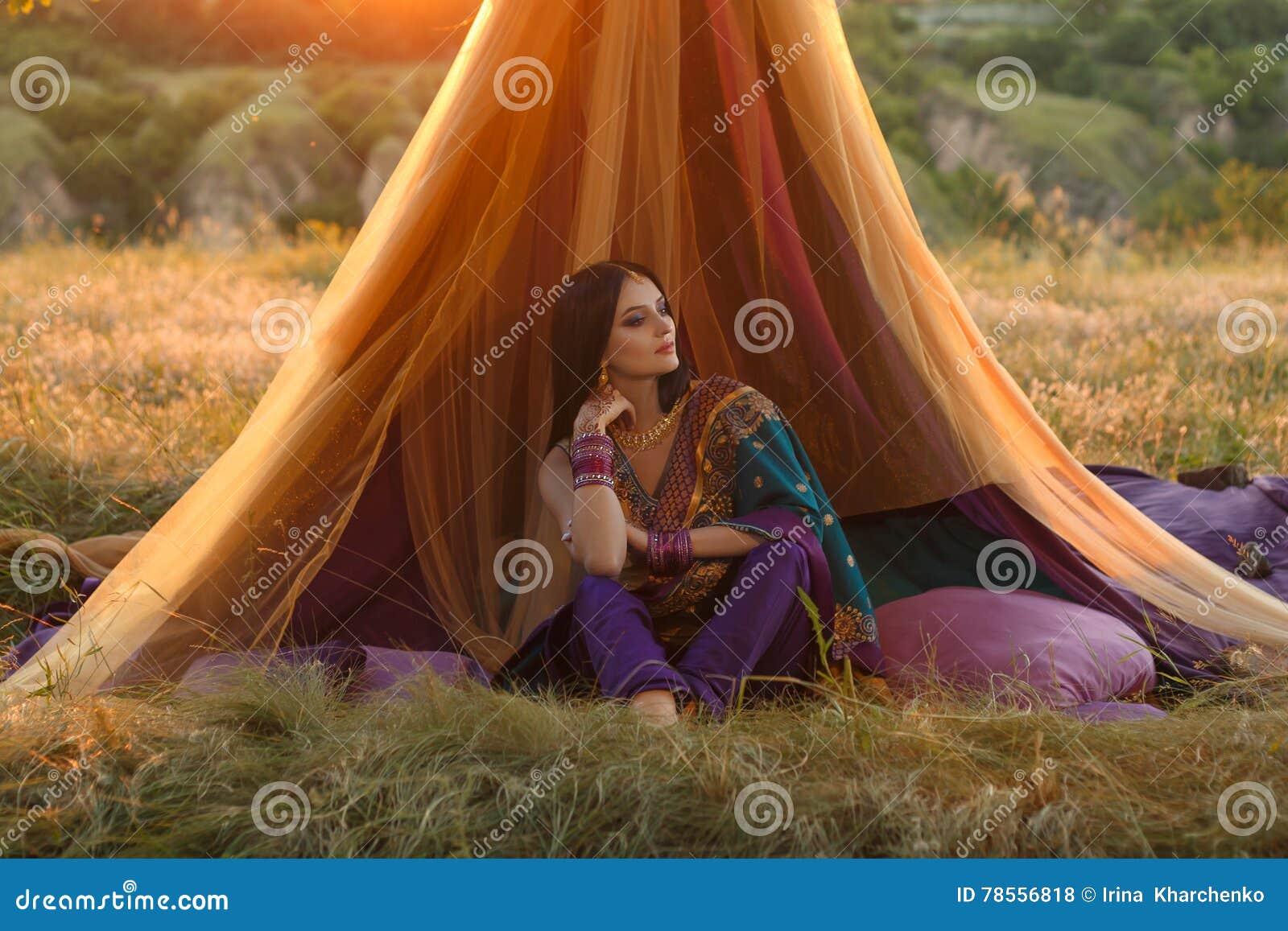 La fille indienne luxueuse s assied dans une tente dehors, au coucher du soleil