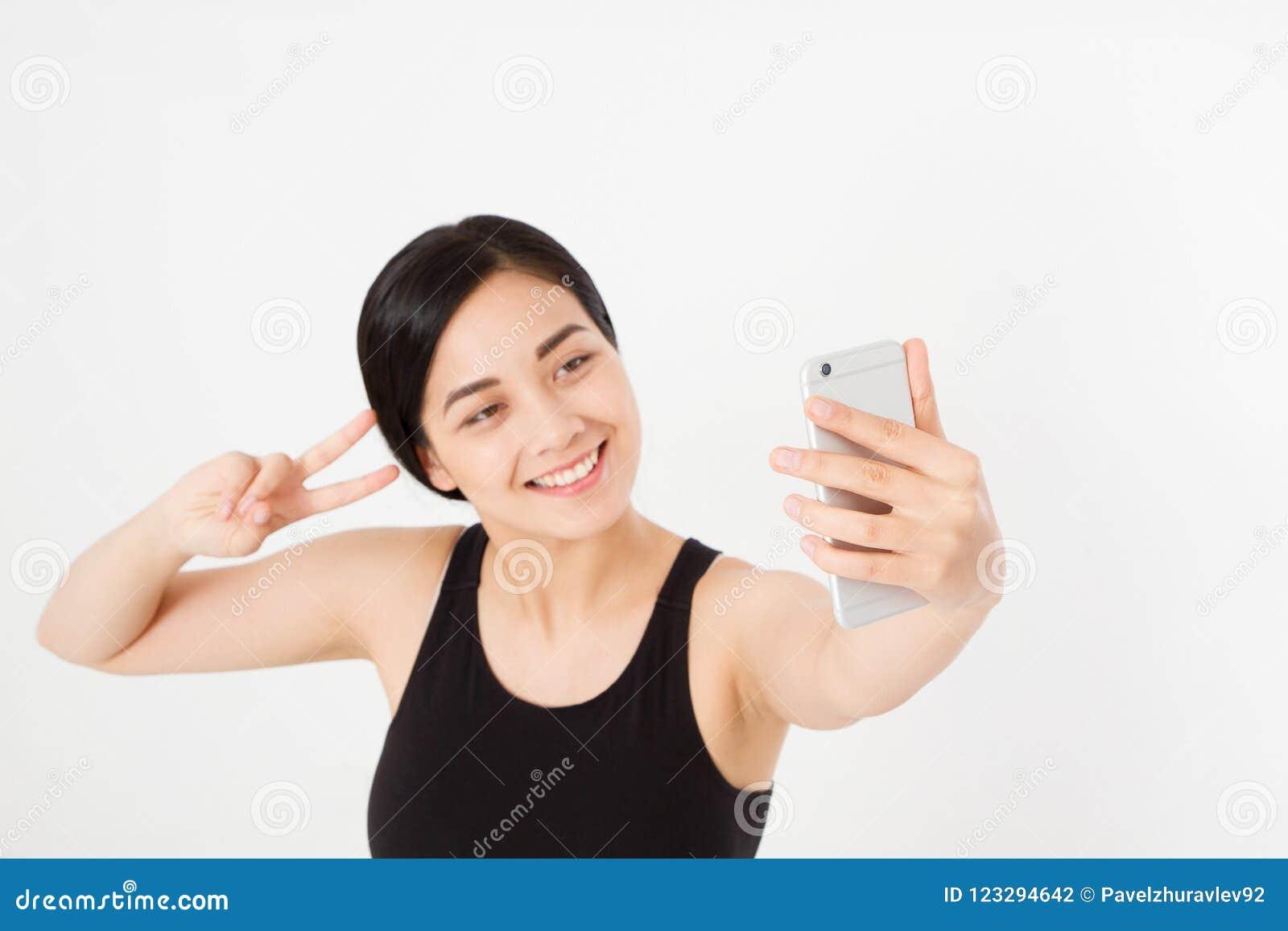 La fille japonaise asiatique de jeune étudiant fait le selfie à son téléphone portable d isolement sur le fond blanc étude ou