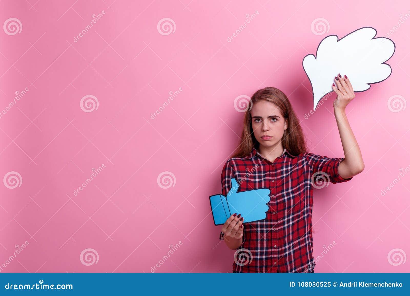 La fille, les prises une image de pensée ou l idée tristes et des pouces lèvent le signe Sur un fond rose