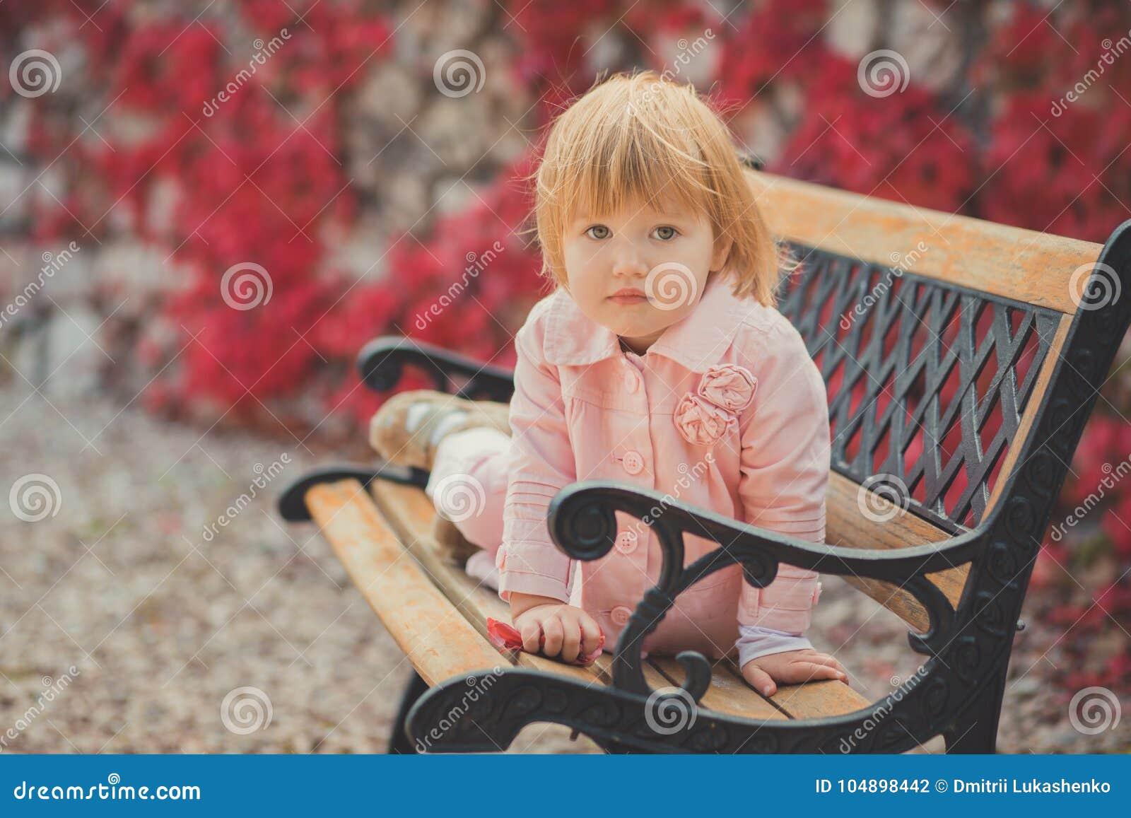 La fille mignonne de bébé avec les cheveux blonds et la joue rose de pomme appréciant l automne de ressort chronomètrent des vaca