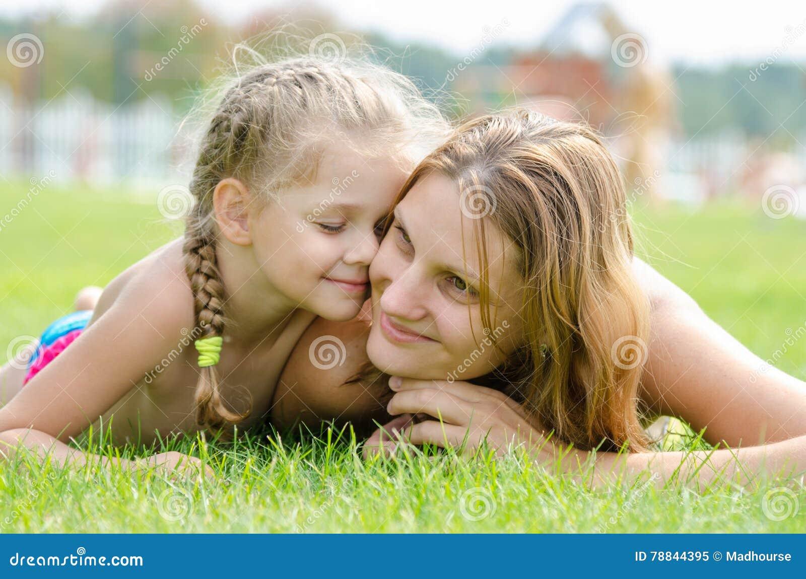La fille mignonne de cinq ans a pressé son visage au mother& x27 ; visage de s sur une pelouse d herbe verte