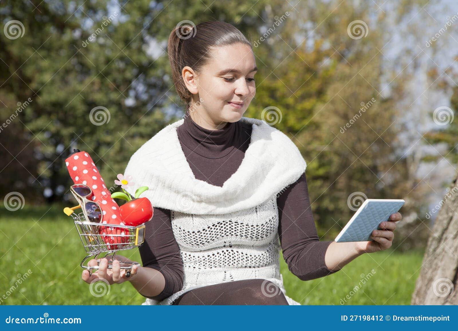 La fille mignonne pense au système en ligne