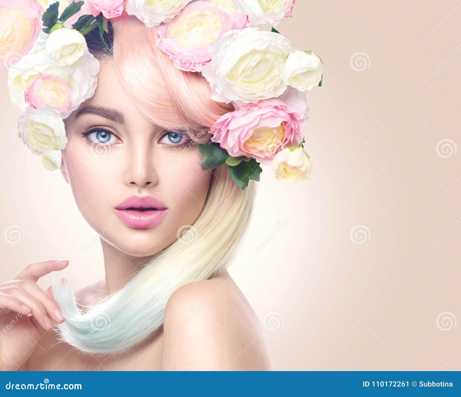 La fille modèle de beauté avec les fleurs colorées tressent et les cheveux colorés Fleurit la coiffure