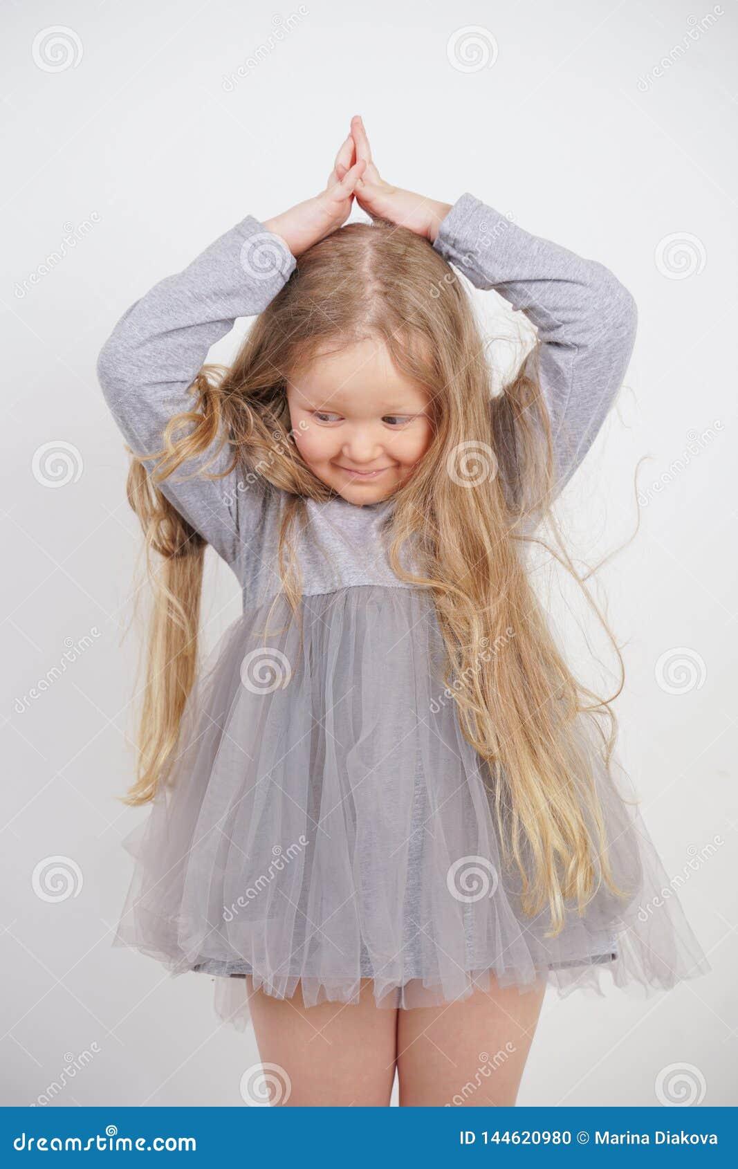 La fille orpheline mignonne tient et tient ses mains au-dessus de sa tête sous forme de maison, rêvant d un appartement, sur un