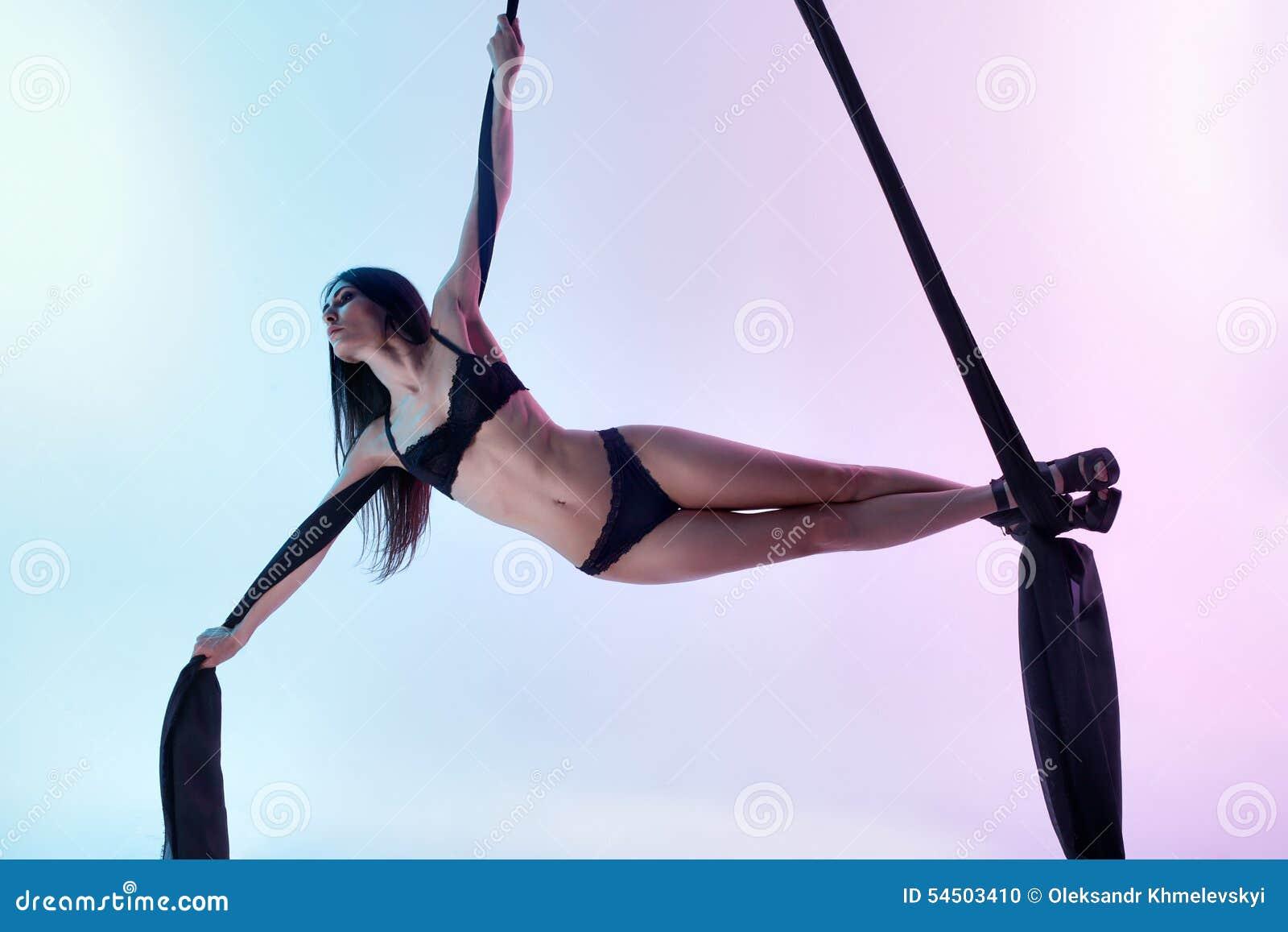 La fille pilote le tissu acrobatique