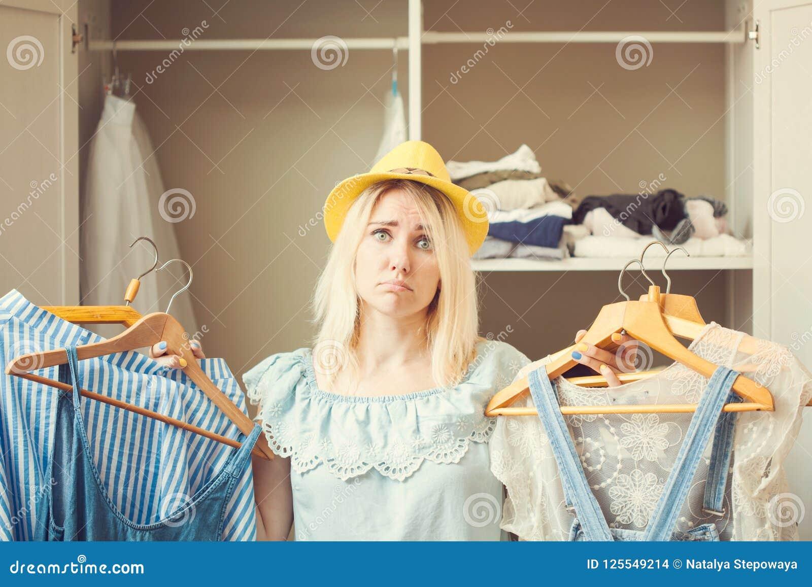 La fille près d une garde-robe avec des vêtements ne peut pas choisir quoi porter Le concept bien choisi lourd n a rien à porter