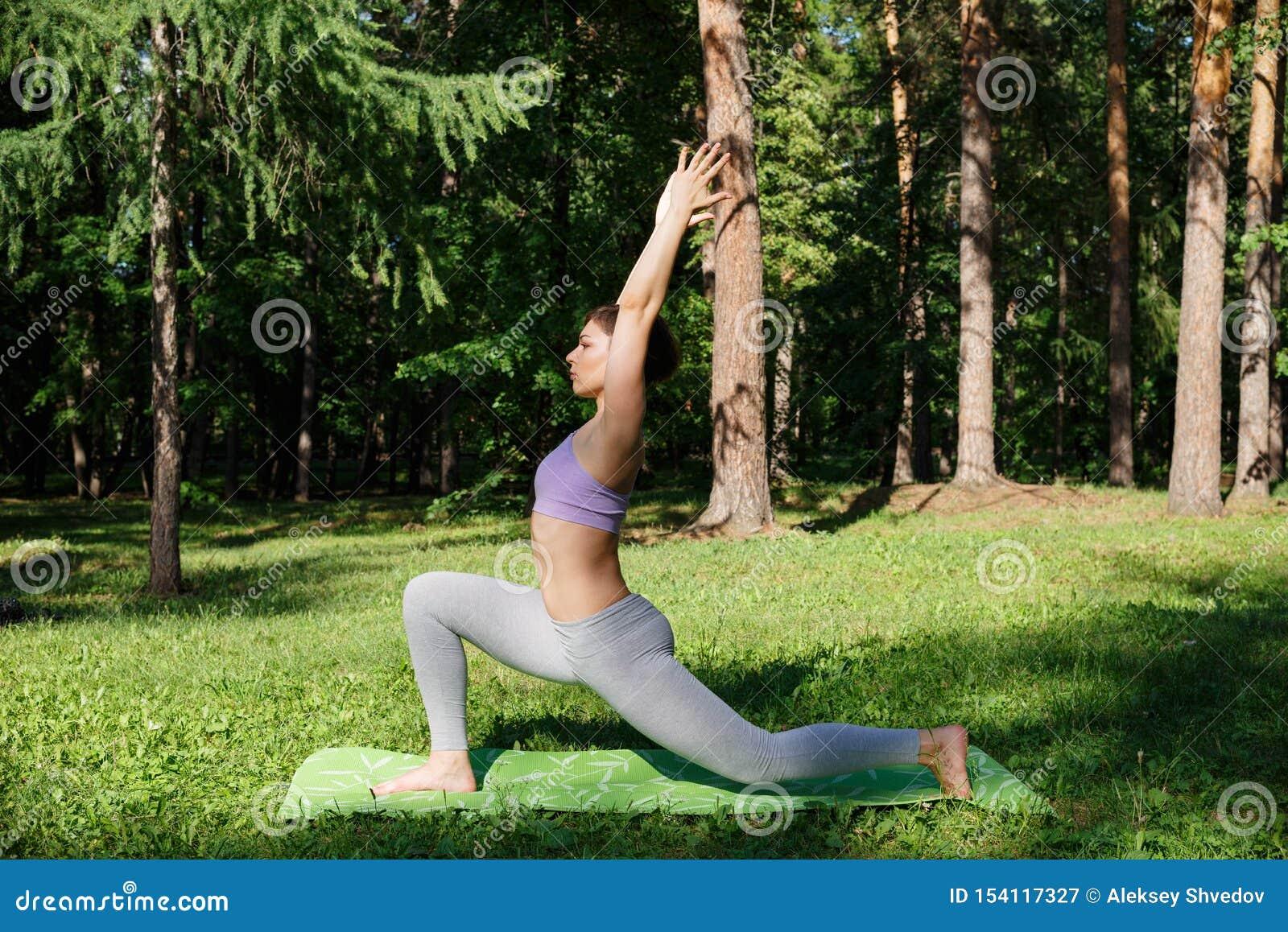 La fille pratique le yoga en parc un jour ensoleillé