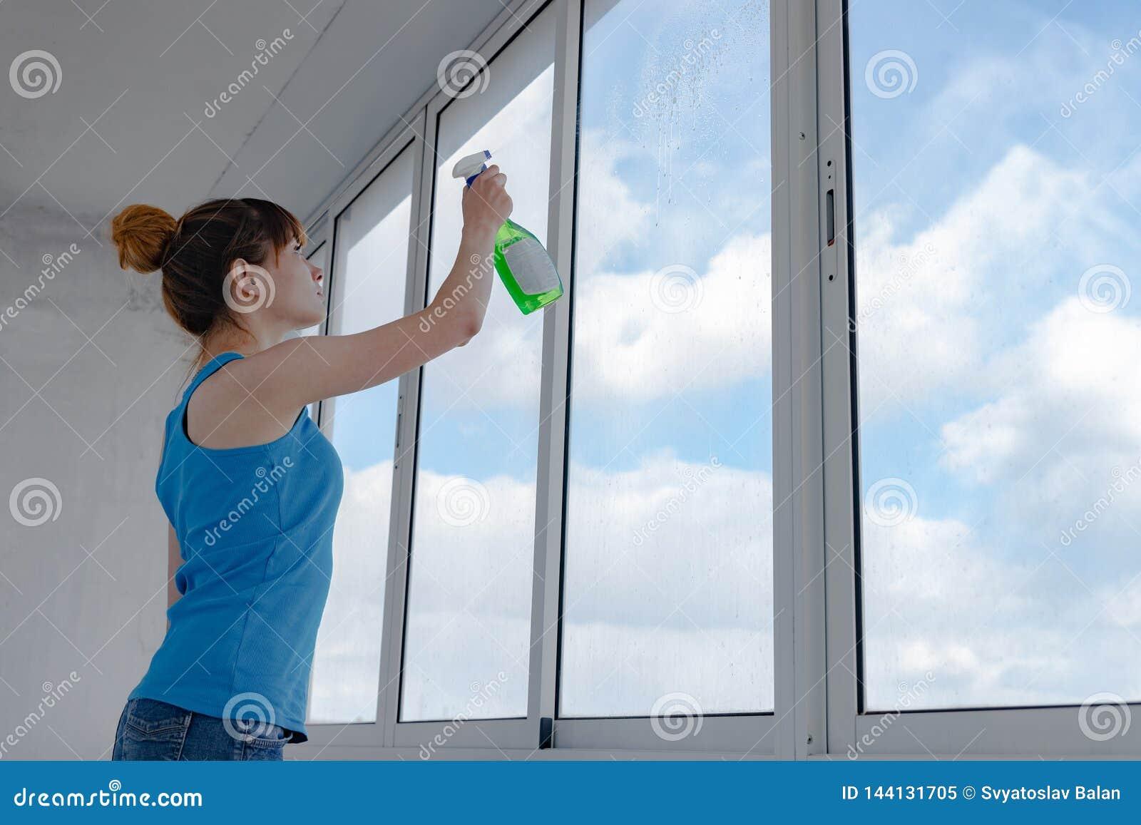 La fille pulvérise le liquide pour les fenêtres de lavage sur le verre sale