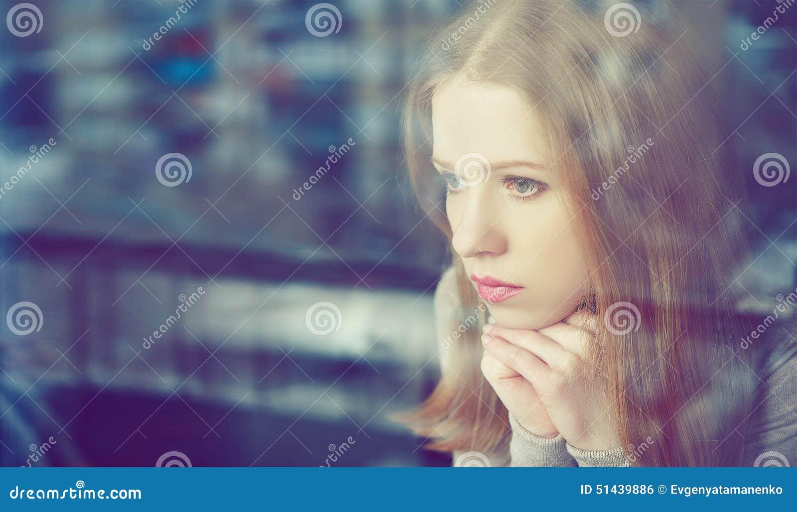 La fille réfléchie de tristesse est triste à la fenêtre