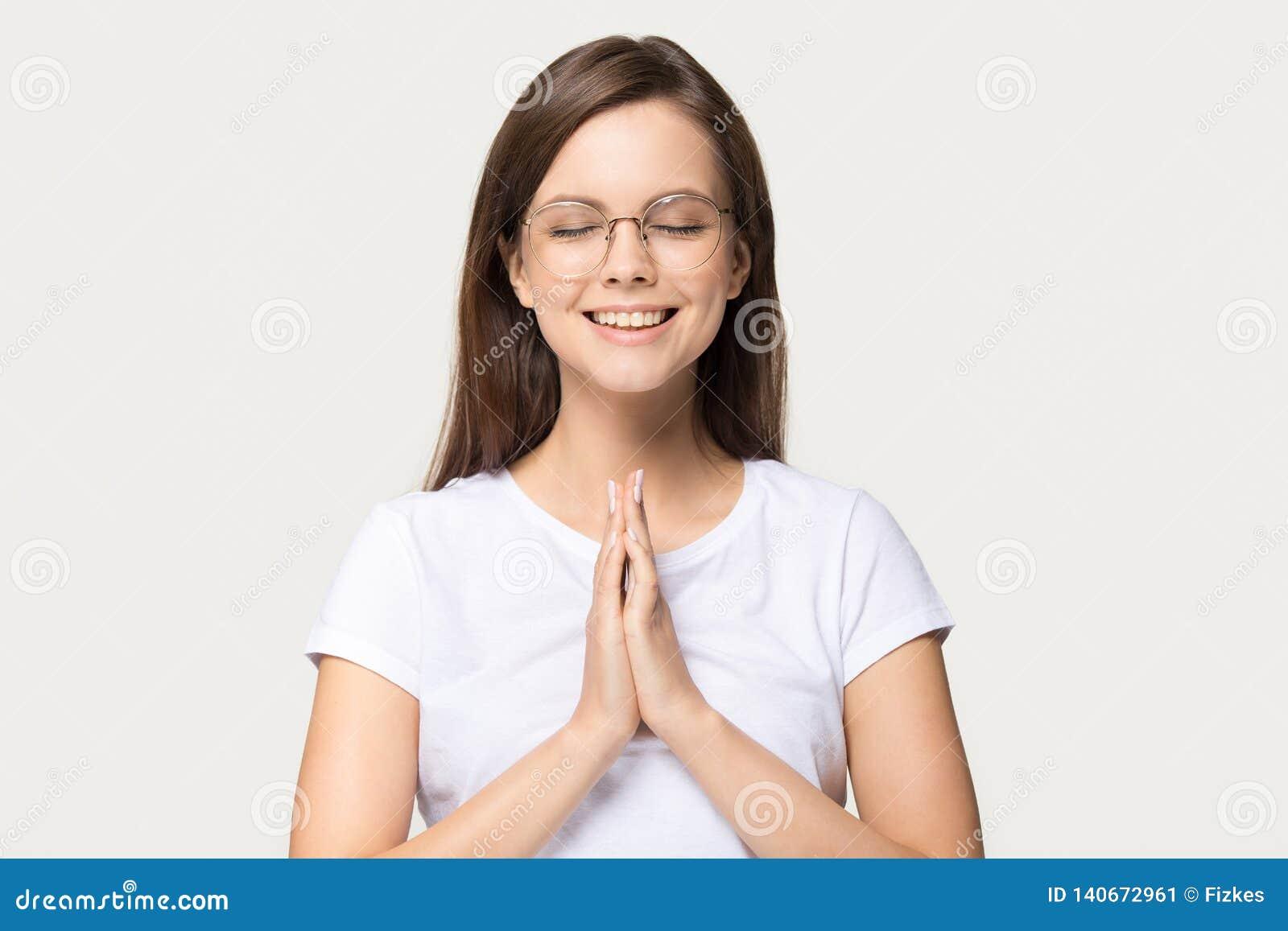 La fille reconnaissante calme heureuse joignent la prière de mains d isolement sur le fond