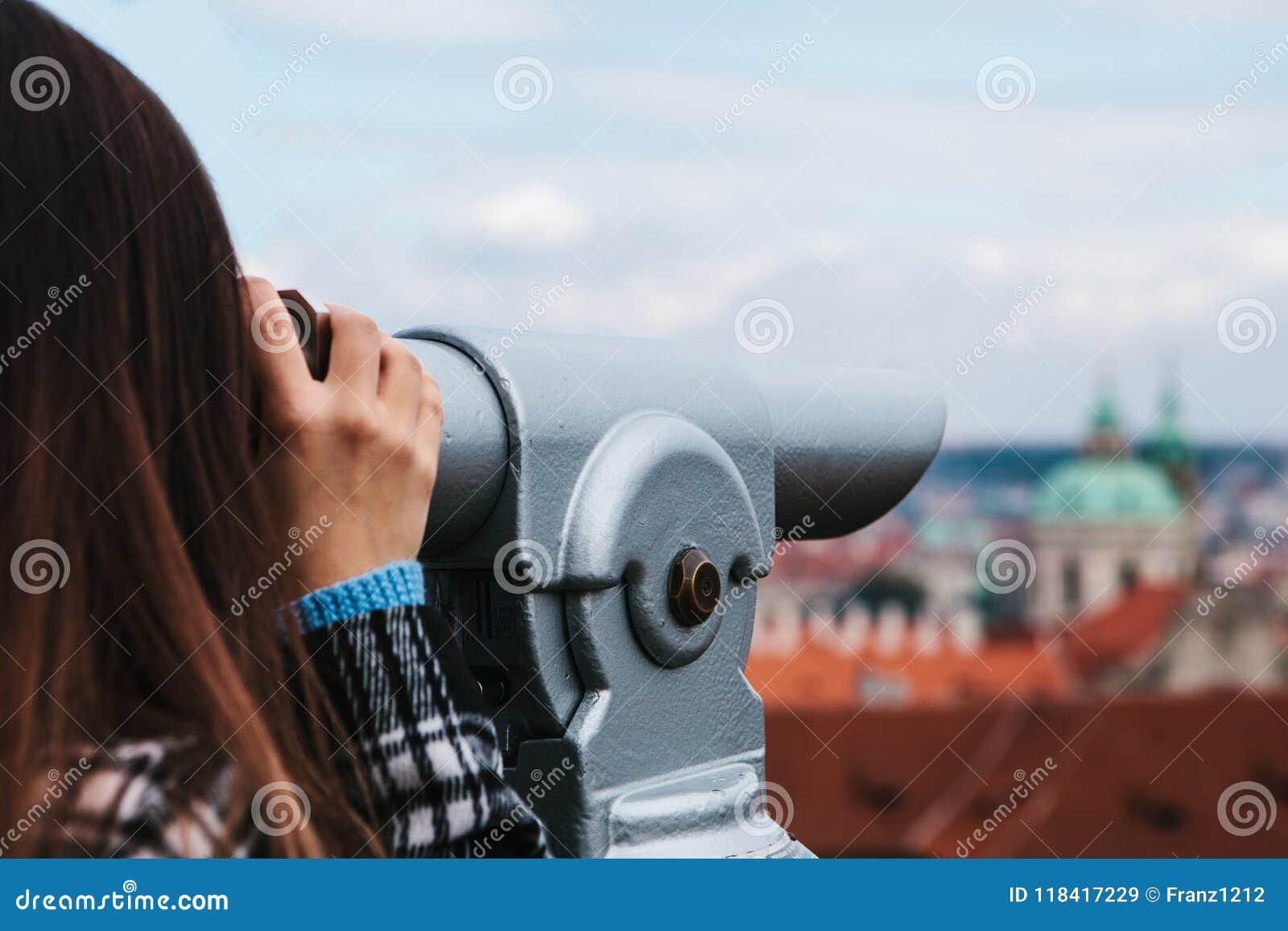 La fille regarde par les jumelles sur la belle architecture de Prague sur le site d observation Prague est un de