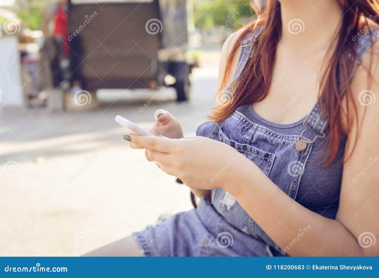 La fille repose sur un banc dans les combinaisons bleues et tient un p mobile