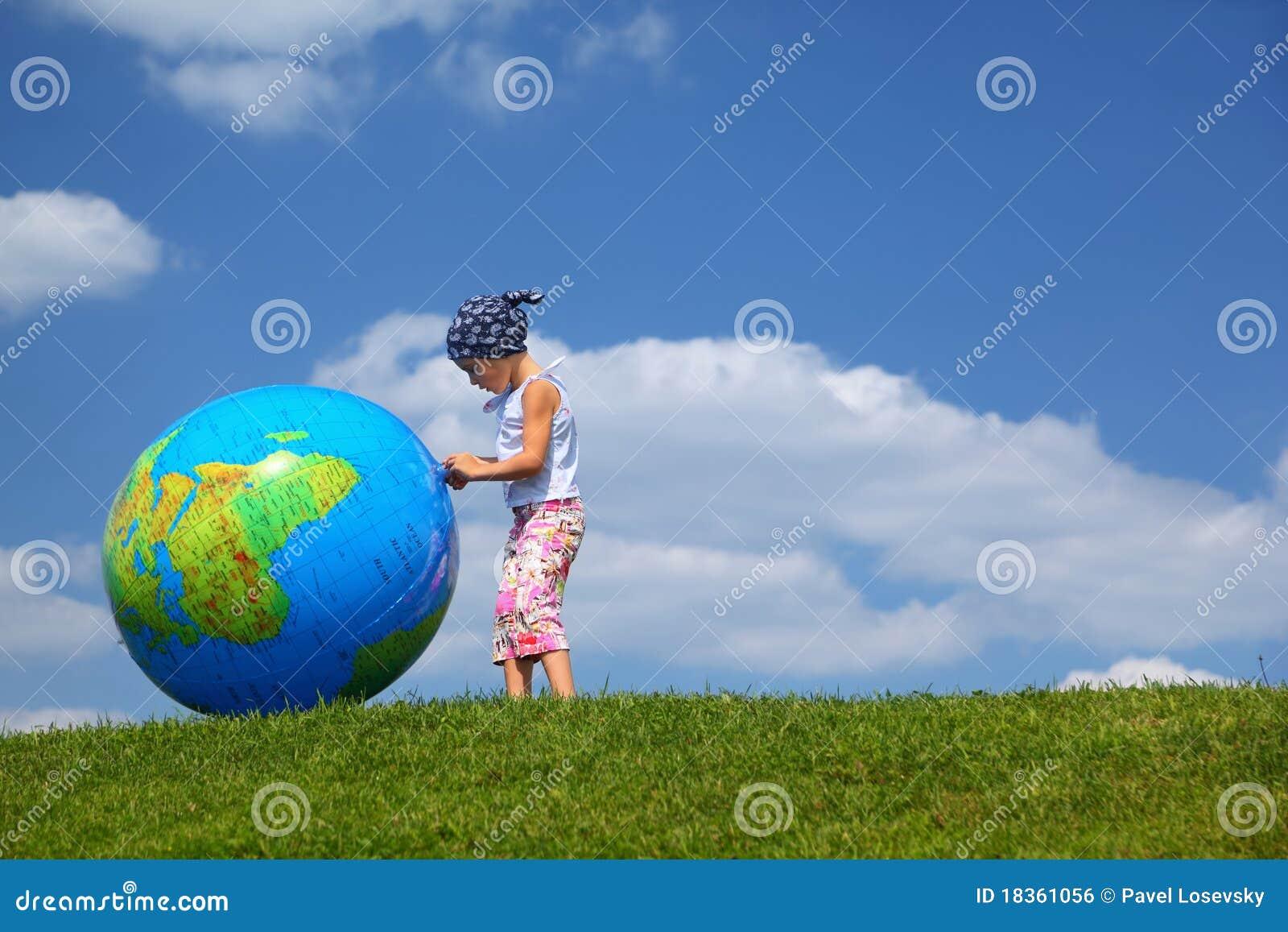 La fille reste sur l herbe et les pièces avec le globe