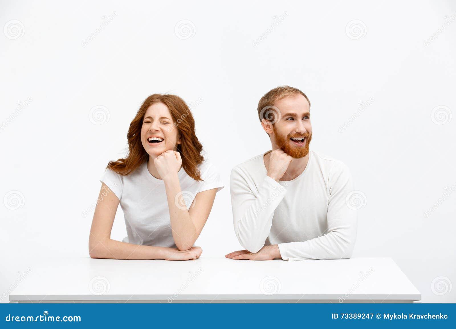 La fille rousse et le garçon de tenderless rient du bureau blanc
