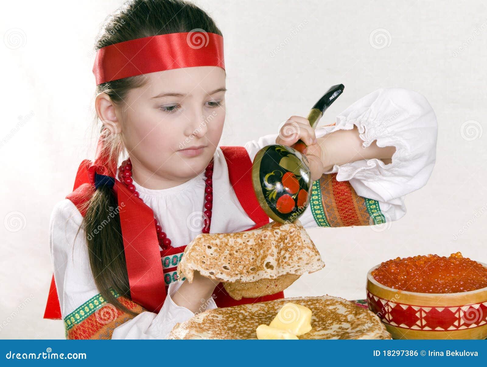 Image libre de droits: la fille russe mange des crêpes avec le caviar