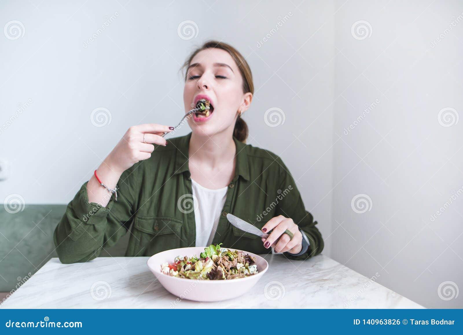 La fille s assied à la table et mange d une salade avec une fourchette La fille mord la salade verte et obtient plumée