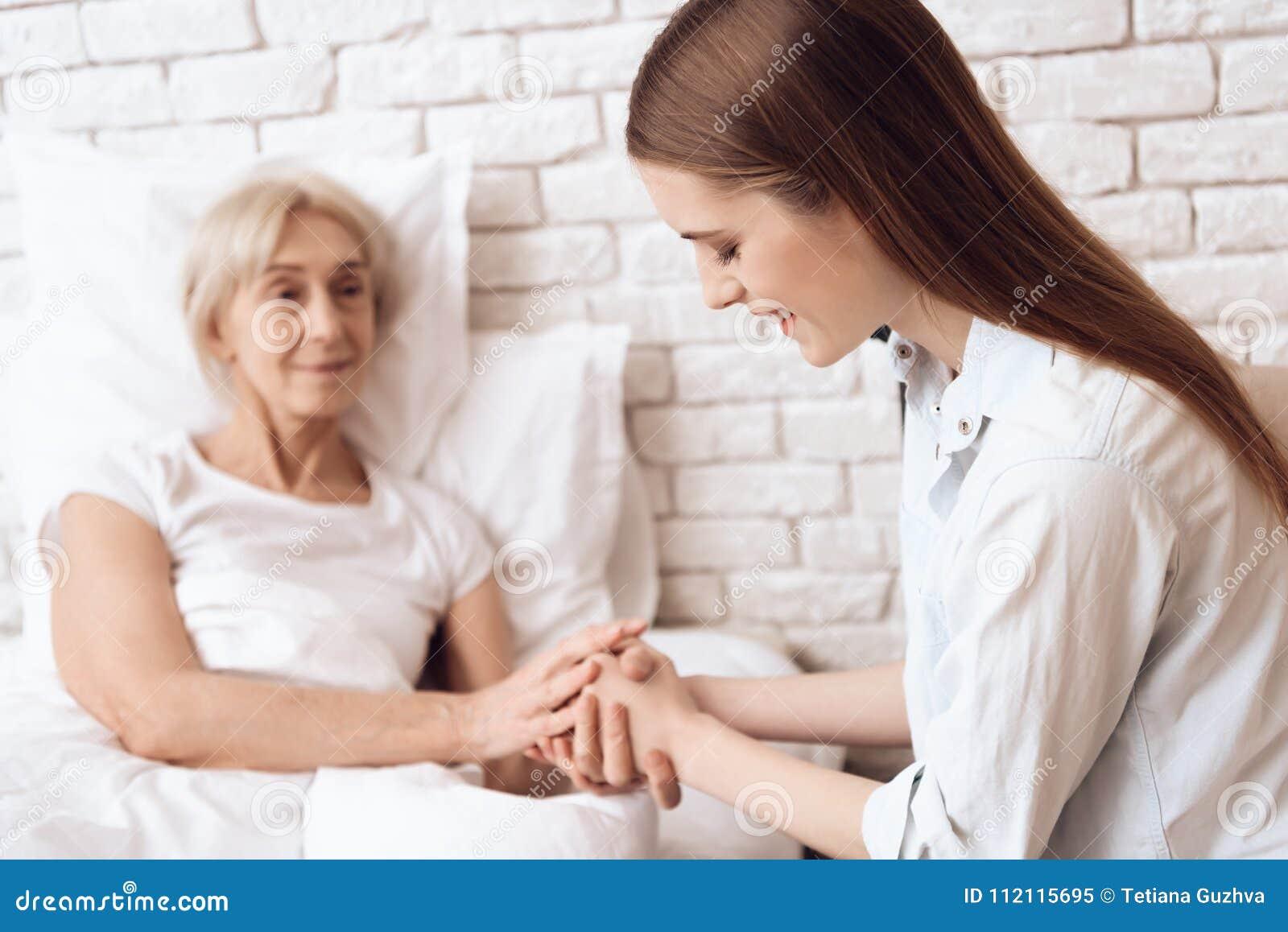 La fille s occupe de la femme agée à la maison Elles tiennent des mains
