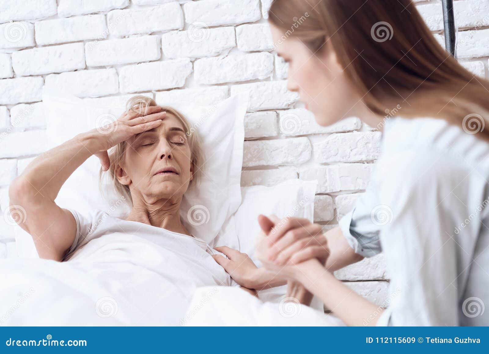 La fille s occupe de la femme agée à la maison Elles tiennent des mains La femme se sent mal
