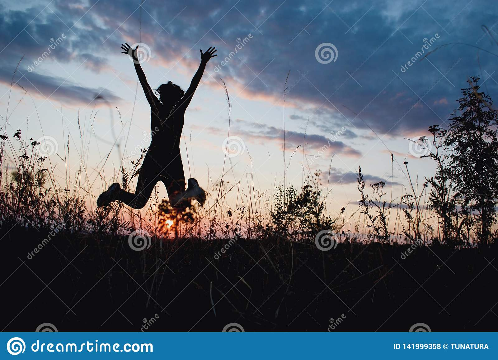 La fille sautant heureusement dans la lumière de coucher du soleil Été, nature, extérieure, liberté, succès, concept de bonheur