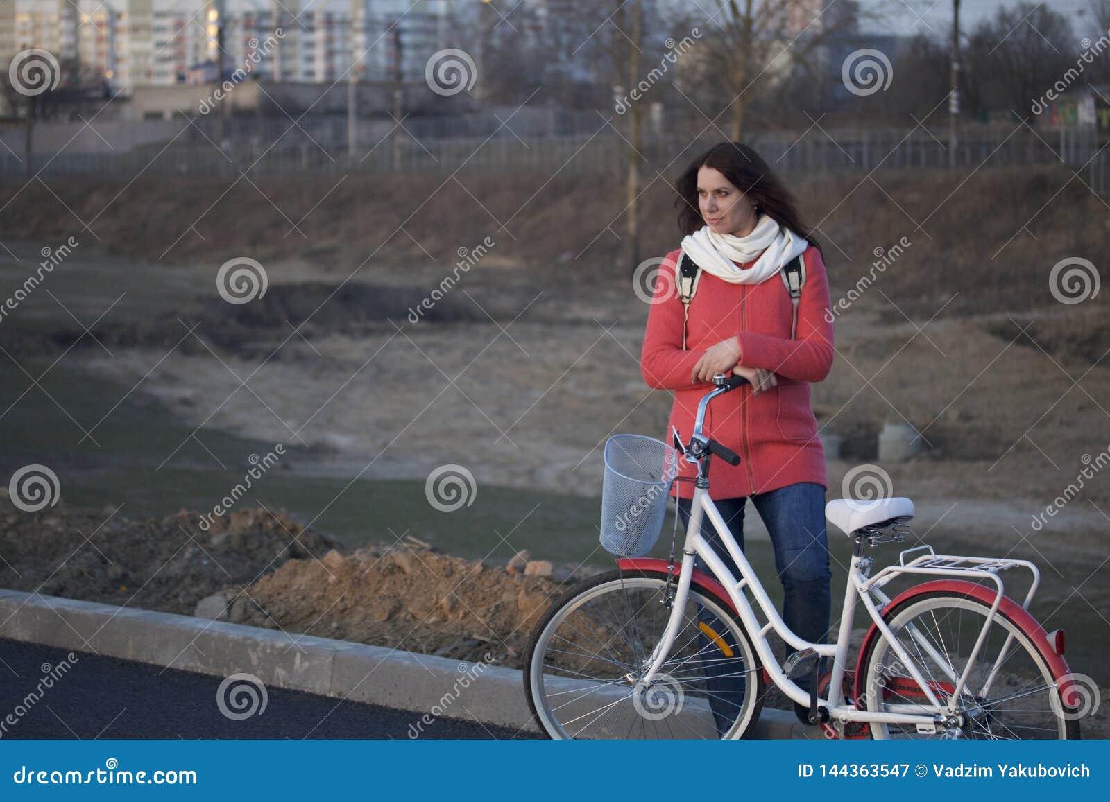 La fille se penche sur un vélo garé Repos sur le cycle de ressort