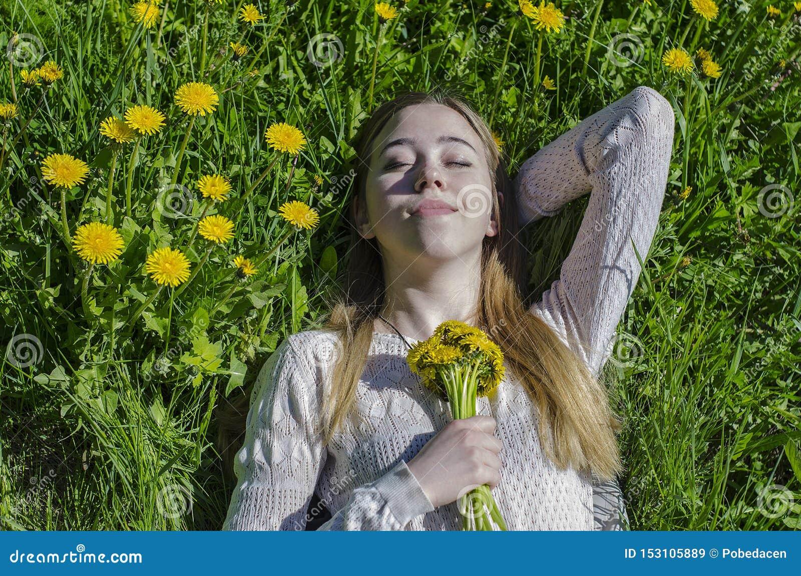 La fille se situe dans une clairière avec un bouquet des pissenlits