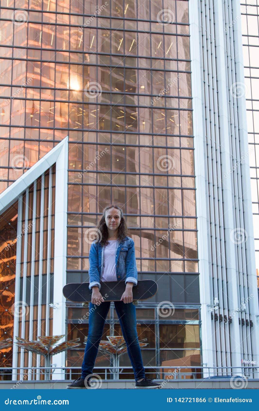 La fille se tient près d un bâtiment tenant un panneau de patin dans une ville près d un édifice haut