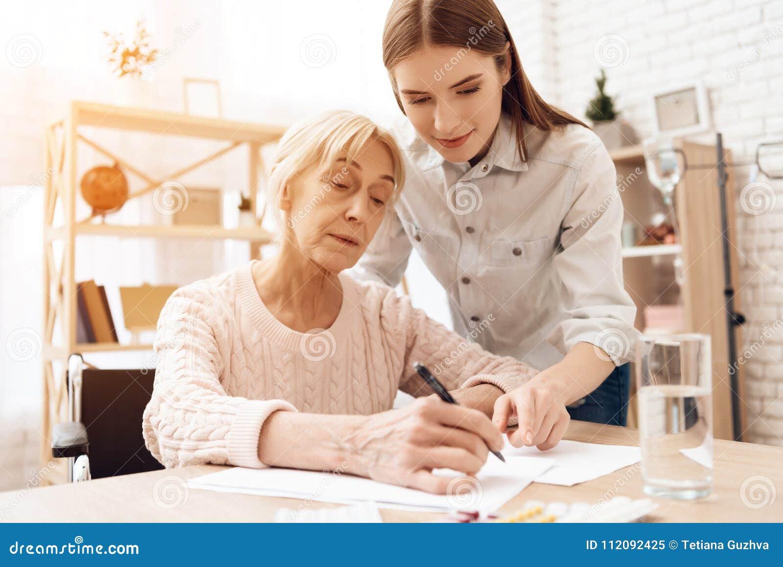 La fille soigne la femme agée à la maison La fille aide la femme écrivent