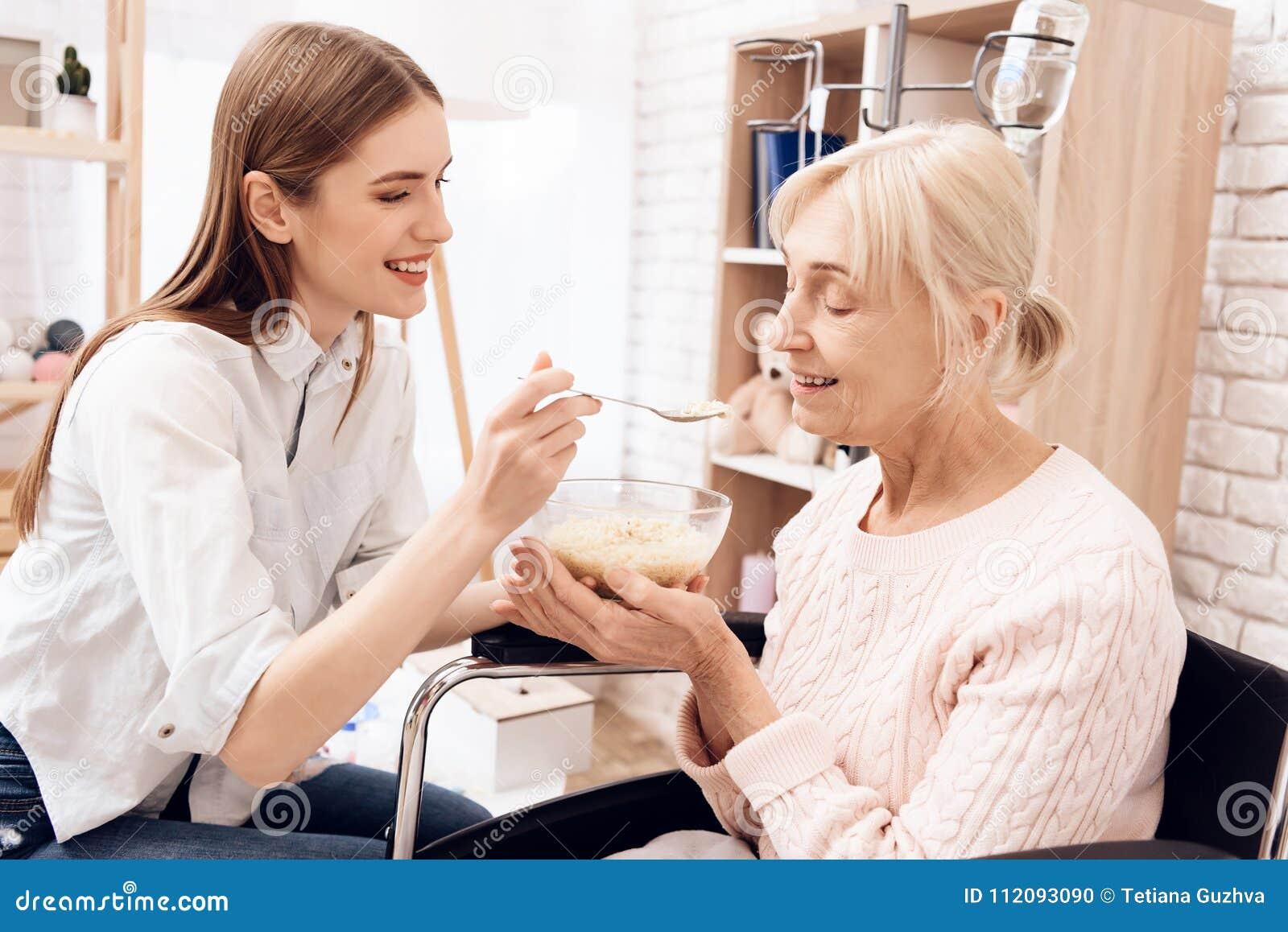 La fille soigne la femme agée à la maison La fille aide la femme avec le dîner