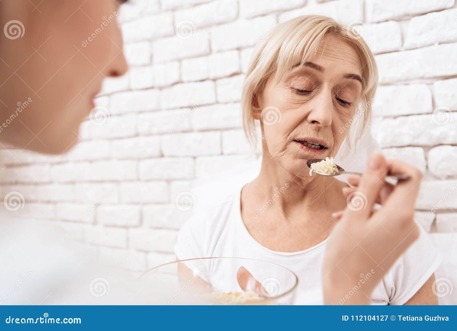 La fille soigne la femme agée à la maison La fille aide la femme avec la nourriture