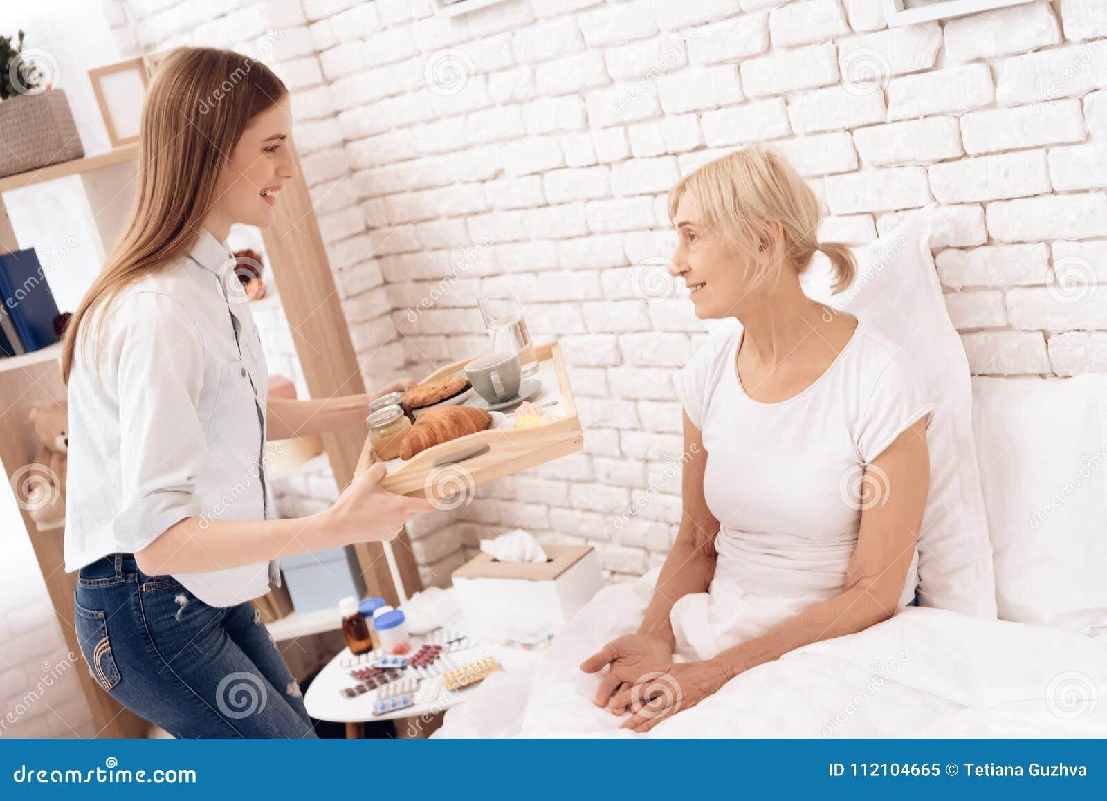 La fille soigne la femme agée à la maison La fille apporte le petit déjeuner sur le plateau