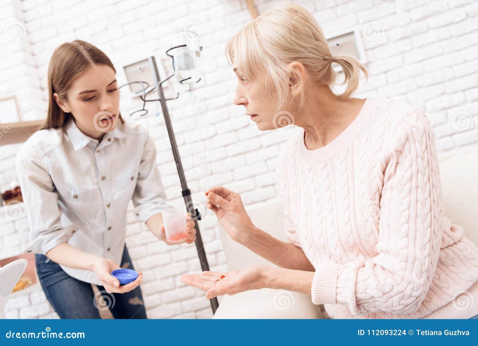 La fille soigne la femme agée à la maison La fille donne à femme ses pilules